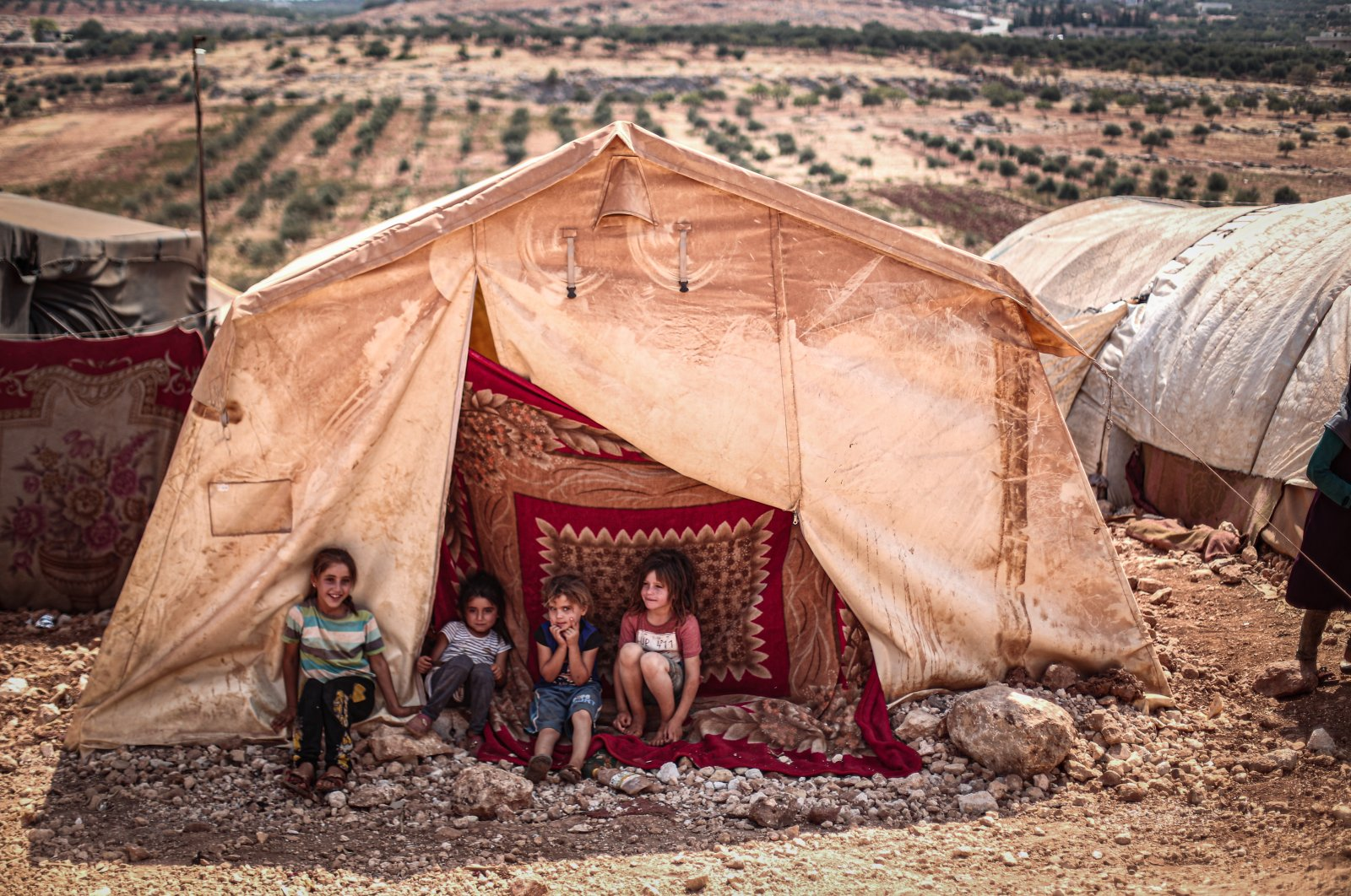 Syrian refugee children sit in front of a tent in Tıy refugee camp of Idlib, Sept.3, 2020. (AA)
