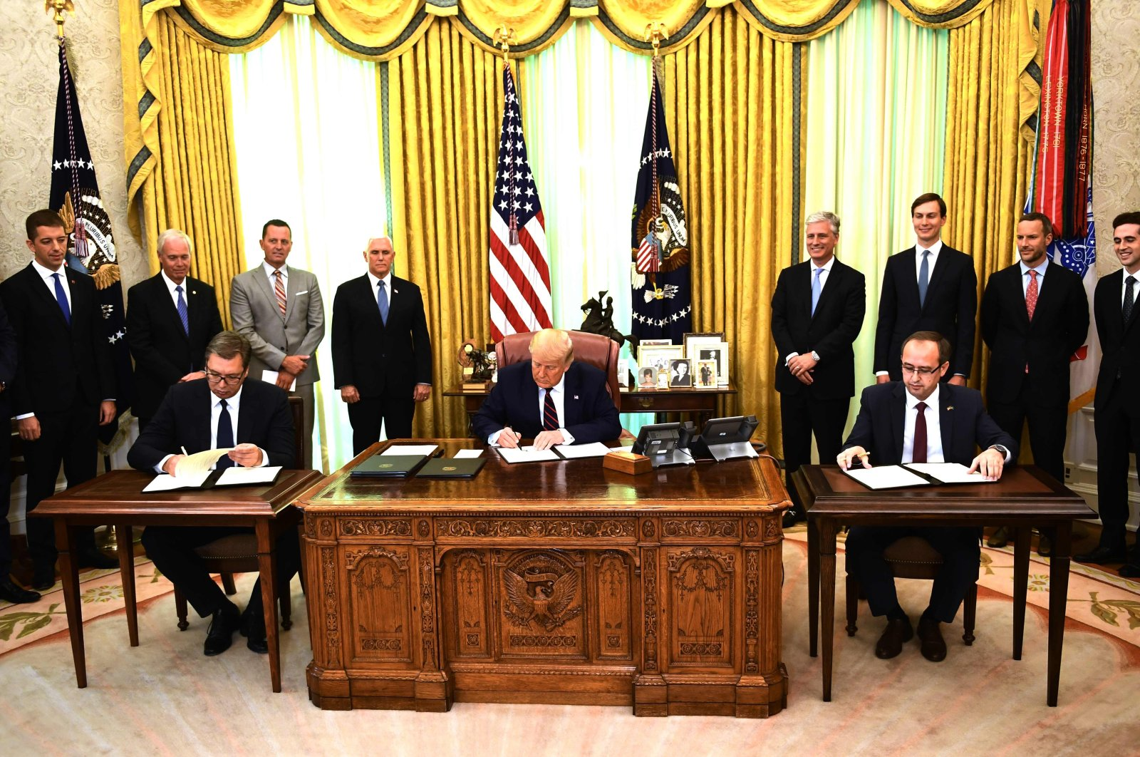 U.S. President Donald Trump signs a document as Kosovar Prime Minister Avdullah Hoti (R) and Serbian President Aleksandar Vucic (L)  sign an agreement on opening economic relations, in the Oval Office of the White House in Washington, D.C., on Sept. 4, 2020. (AFP Photo)
