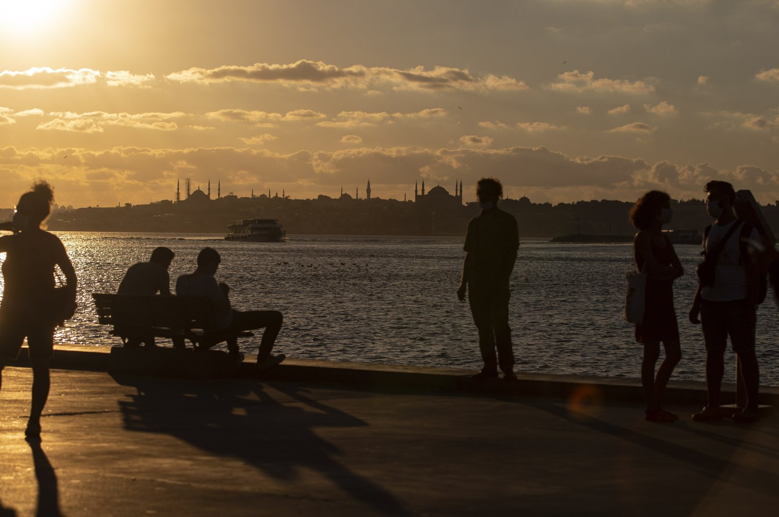 People enjoy the sunset near the Bosporus in front of the Hagia Sophia Grand Mosque and the Blue Mosque in Istanbul, Turkey, Aug. 5, 2020. (EPA Photo)