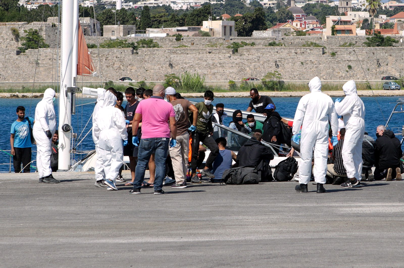 Healthcare professionals in protective suits make tests for COVID-19 to migrants at the port of Rhodes Island, Dodecanese, Greece, 28 August 2020. (EPA Photo)