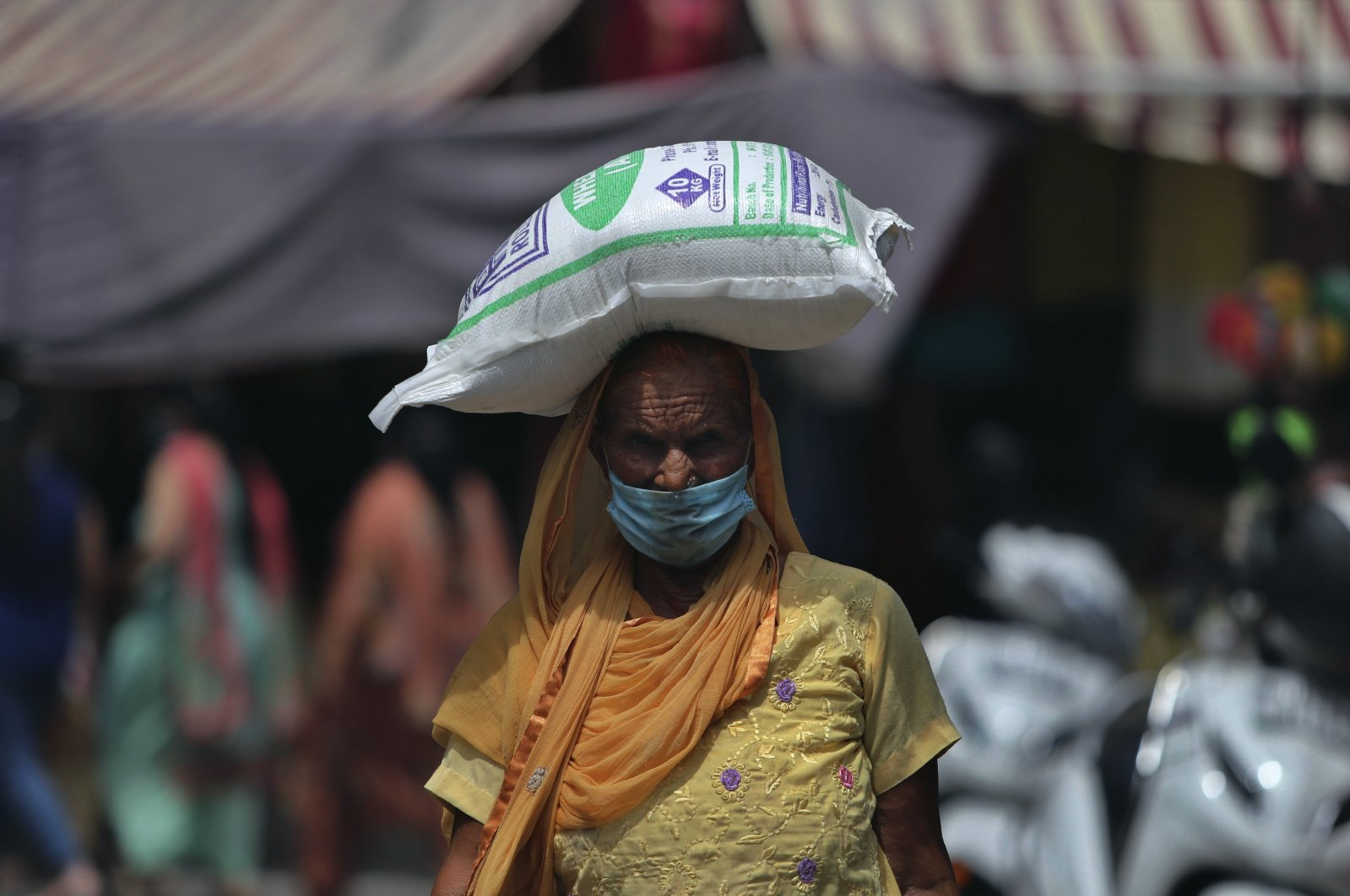 An Indian woman wearing face mask as a precaution against the coronavirus walks carrying a bag of flour on her head  in Jammu, India, Thursday, Aug 6, 2020. (AP Photo)