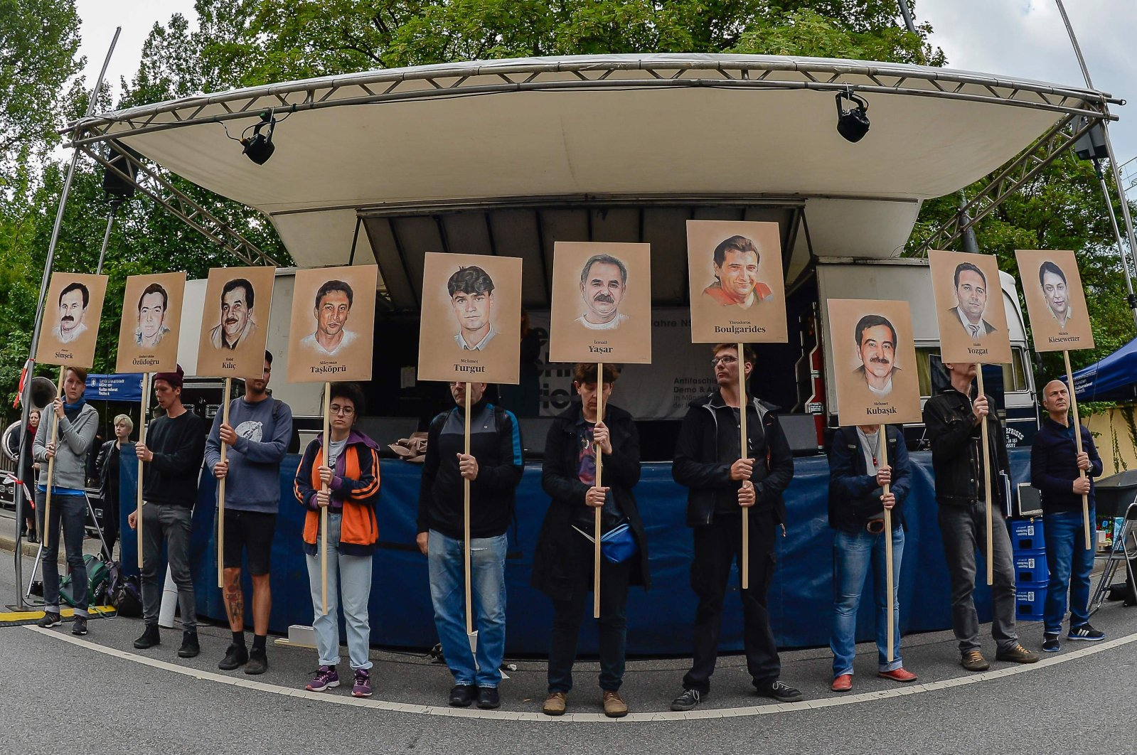 Protesters hold up signs with pictures of the victims of Neo-Nazi cell National Socialist Underground (NSU) before the proclamation of sentence in the trial against Beate Zschaepe, the only surviving member of the NSU behind a string of racist murders, in Munich, July 11, 2018. (AFP Photo)