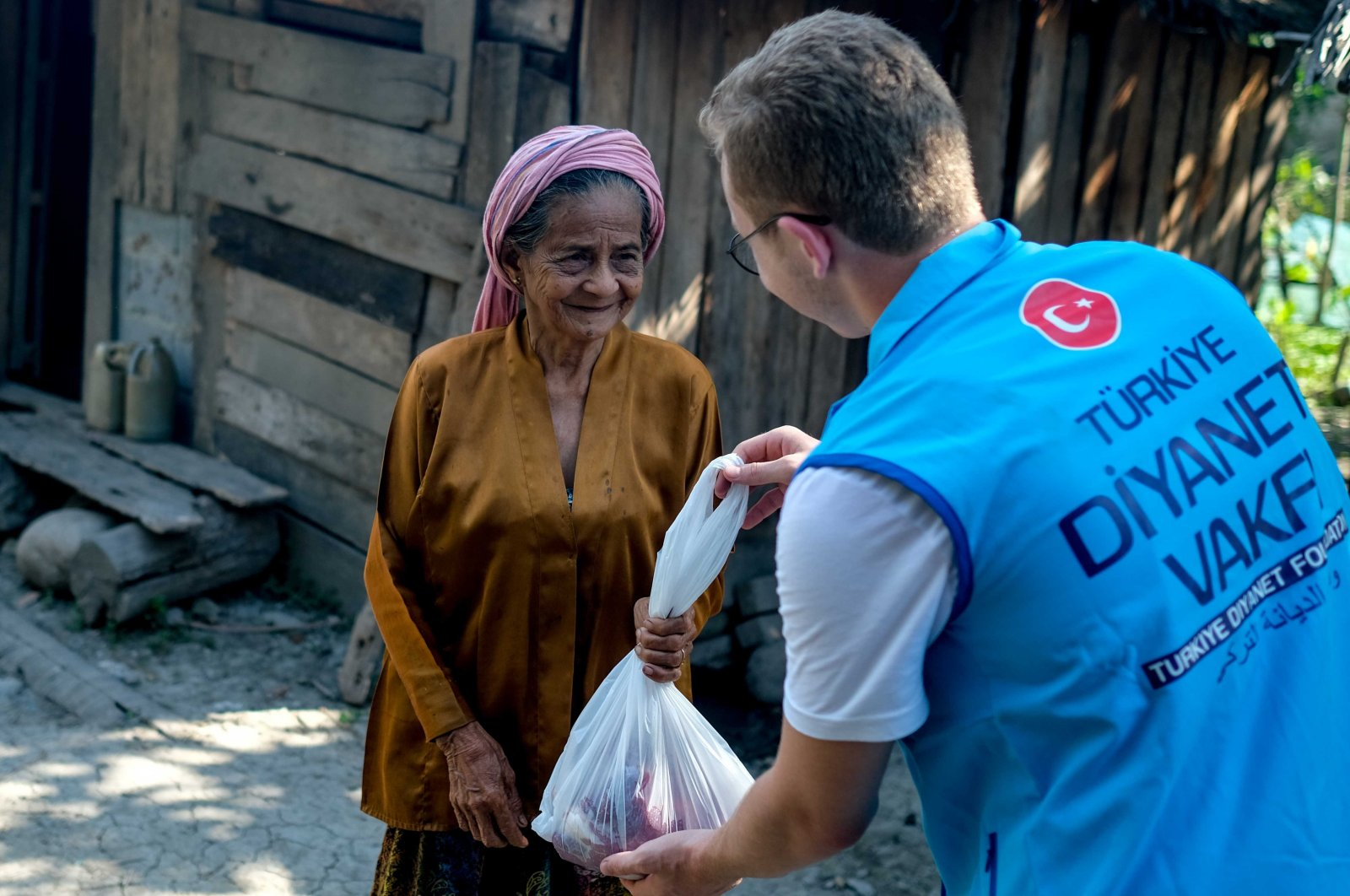 A Türkiye Diyanet Foundation (TDV) volunteer delivers aid to a woman in the Bangsamoro Autonomous Region of the Philippines, Aug. 11, 2019. (AA Photo)