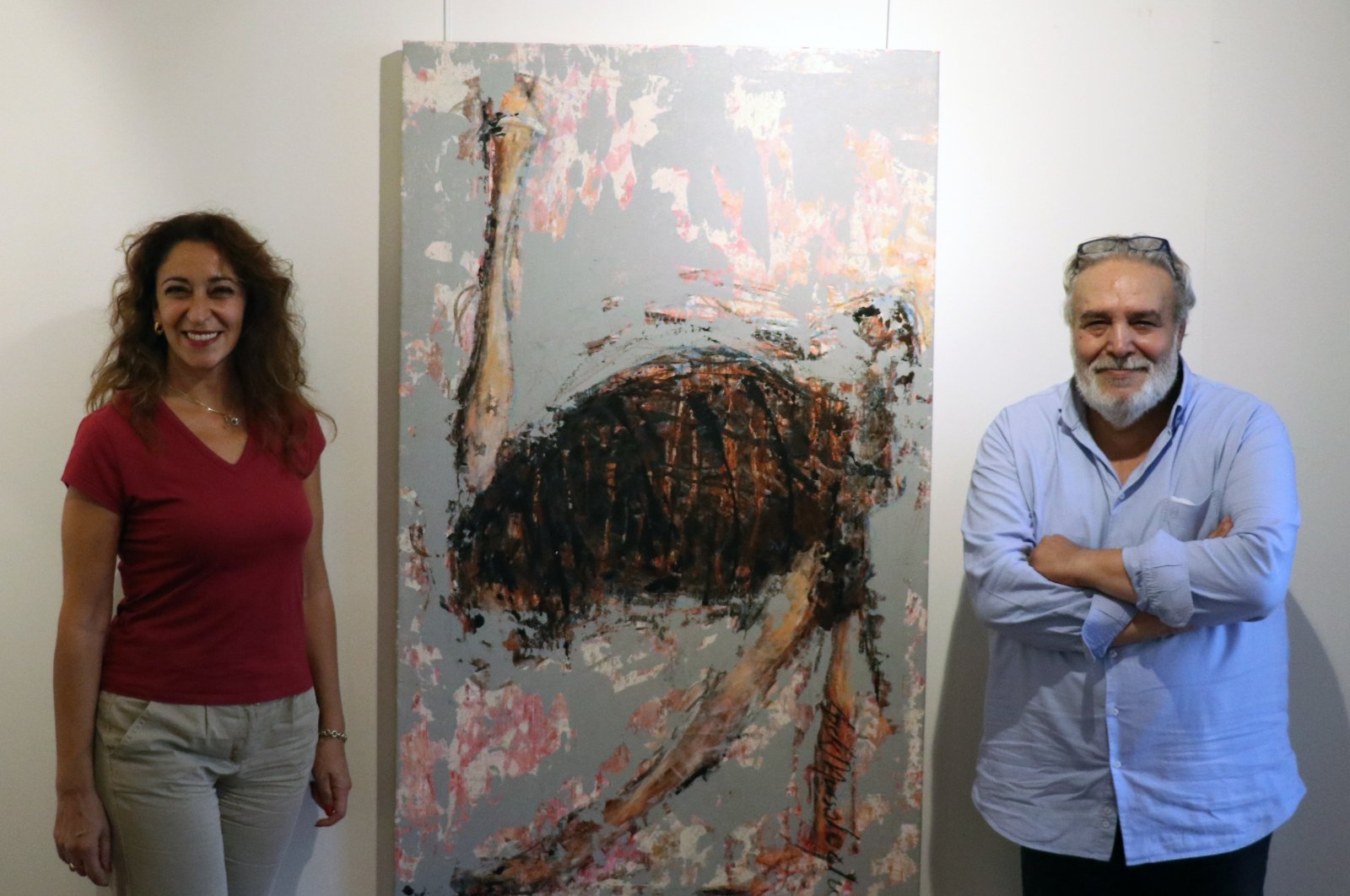 Artist İpek Mursaloğlu (L) and art director Adnan Al Ahmad pose with one of the ostrich paintings at the exhibition, Istanbul, Turkey, Sept. 4, 2020. (AA PHOTO)