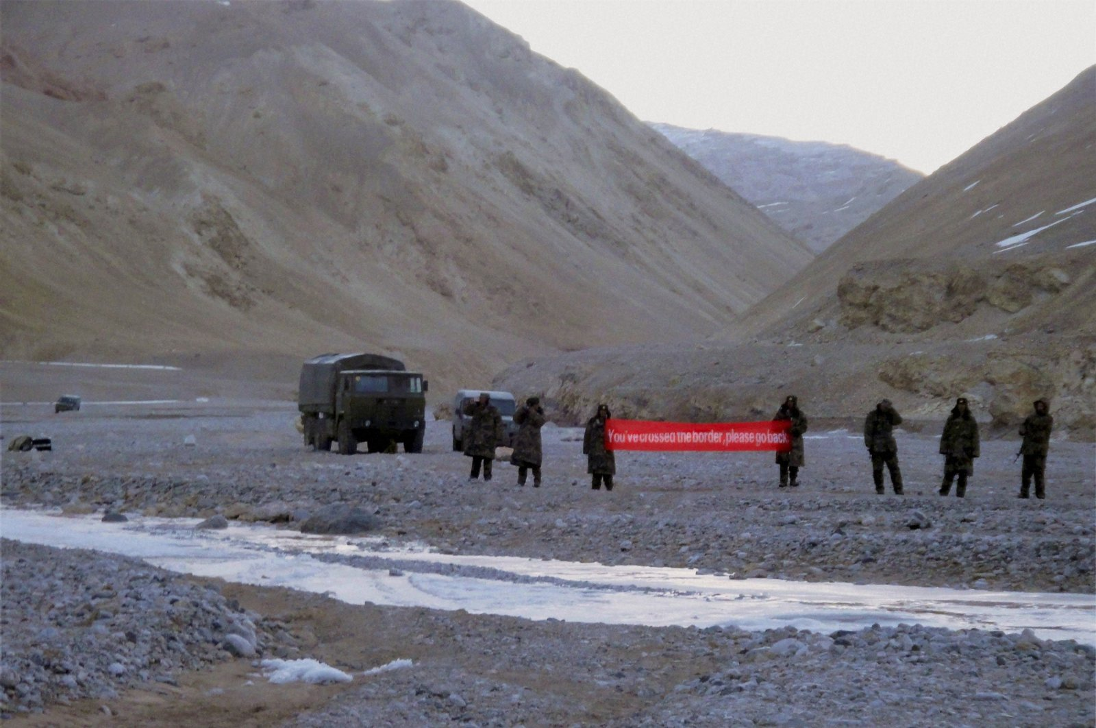 """In this May 5, 2013, file photo, Chinese troop hold a banner which reads: """"You've crossed the border, please go back,"""" in Ladakh, India. (AP Photo)"""
