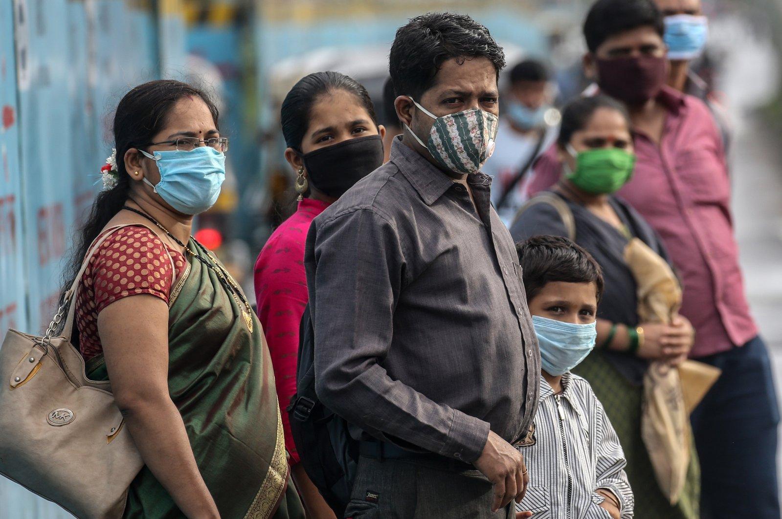 Indian people wearing protective masks wait at bus stop in Mumbai, India, Aug. 23, 2020. (EPA Photo)