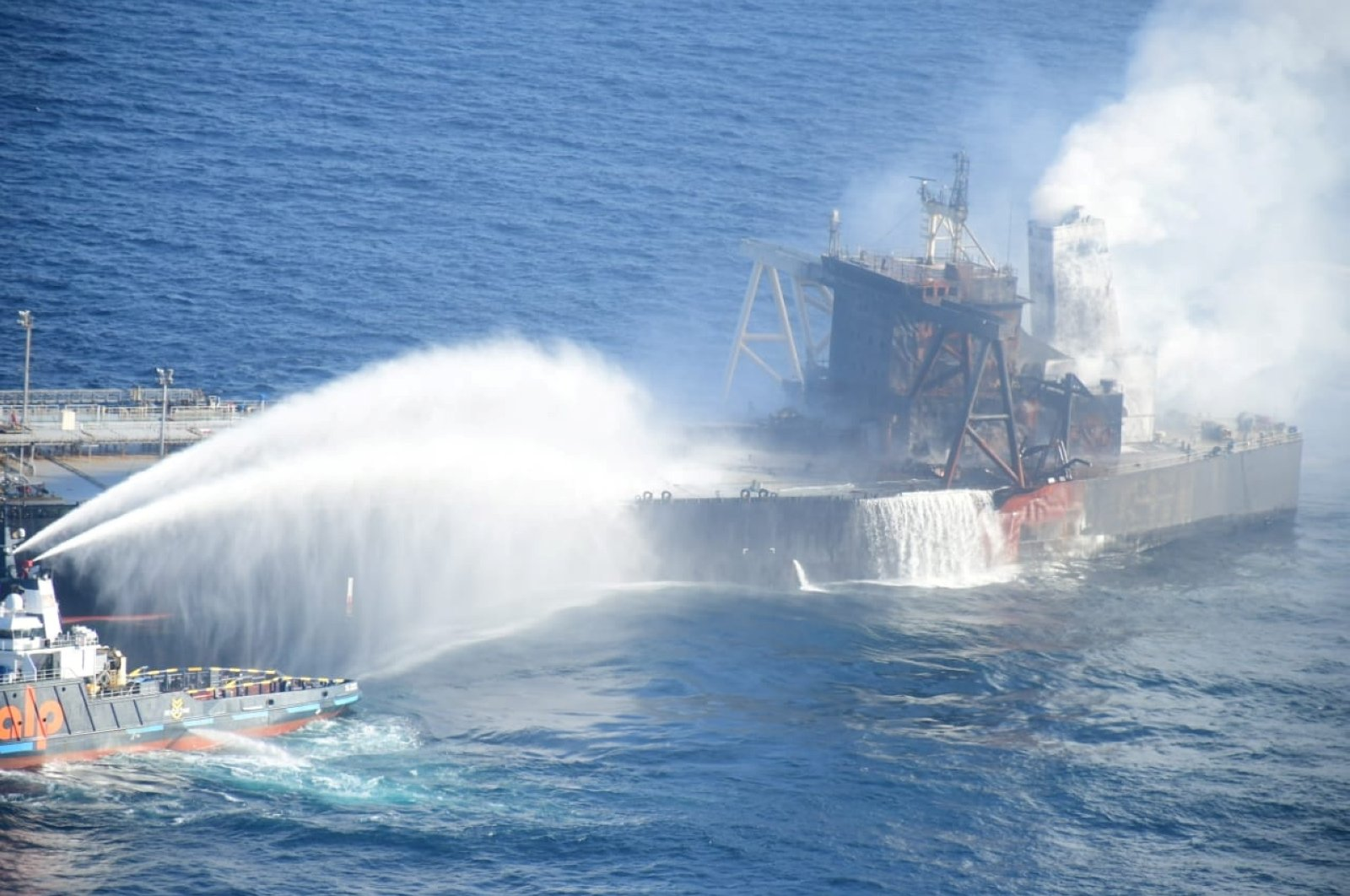A Sri Lanka Navy boat sprays water on the New Diamond, a very large crude carrier (VLCC) chartered by Indian Oil Corp (IOC), that was carrying the equivalent of about 2 million barrels of oil, after a fire broke out off the east coast of Sri Lanka, Sept. 6, 2020. (Sri Lankan Airforce media Photo via Reuters)