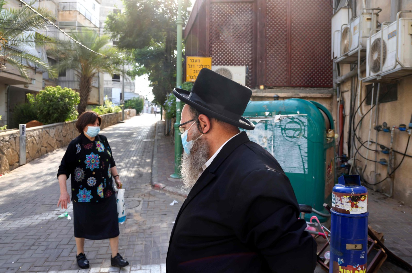 Ultra-Orthodox Jews wearing protective face masks walk in the ultra-Orthodox city of Bnei Brak, near Tel Aviv, on Sept. 6, 2020. (AFP Photo)