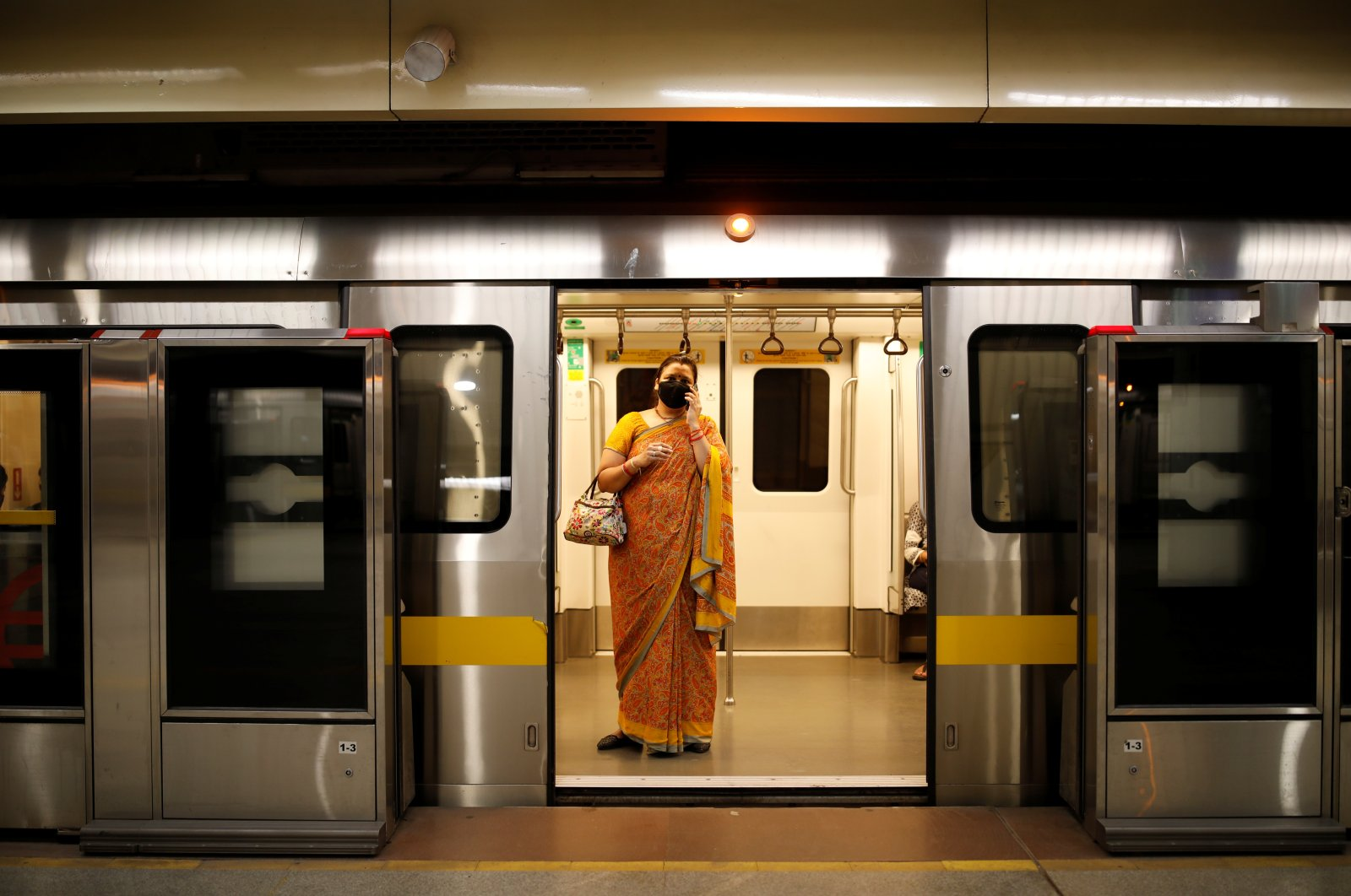 A passenger wearing a face mask takes a train at a Delhi metro station, New Delhi, India, Sept. 7, 2020. (Reuters Photo)
