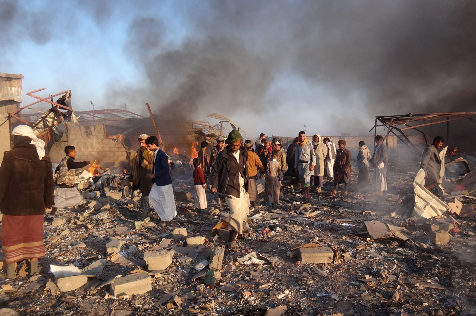 In this file photo taken on Jan. 6, 2018 smoke rises as Yemenis inspect the damage at the site of airstrikes in the northwestern Huthi-held city of Saada. (AFP Photo)