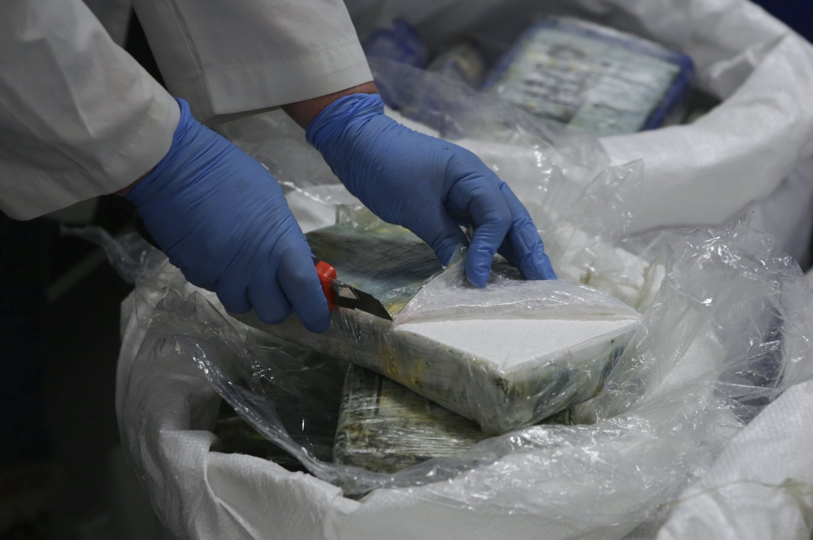 A member of the police opens a packet with cocaine as a large supply recently seized is displayed to the press at the Portuguese police headquarters in Lisbon, Jan. 8, 2020. (AP Photo)