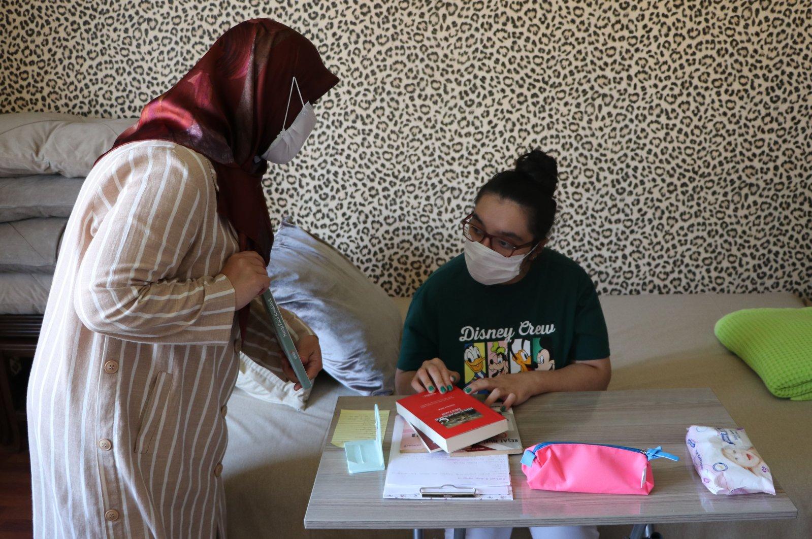 A municipality official delivers books to Beyzanur Yaren Şireli (R) in Kahramanmaraş, southern Turkey, Sept. 7, 2020. (AA Photo)