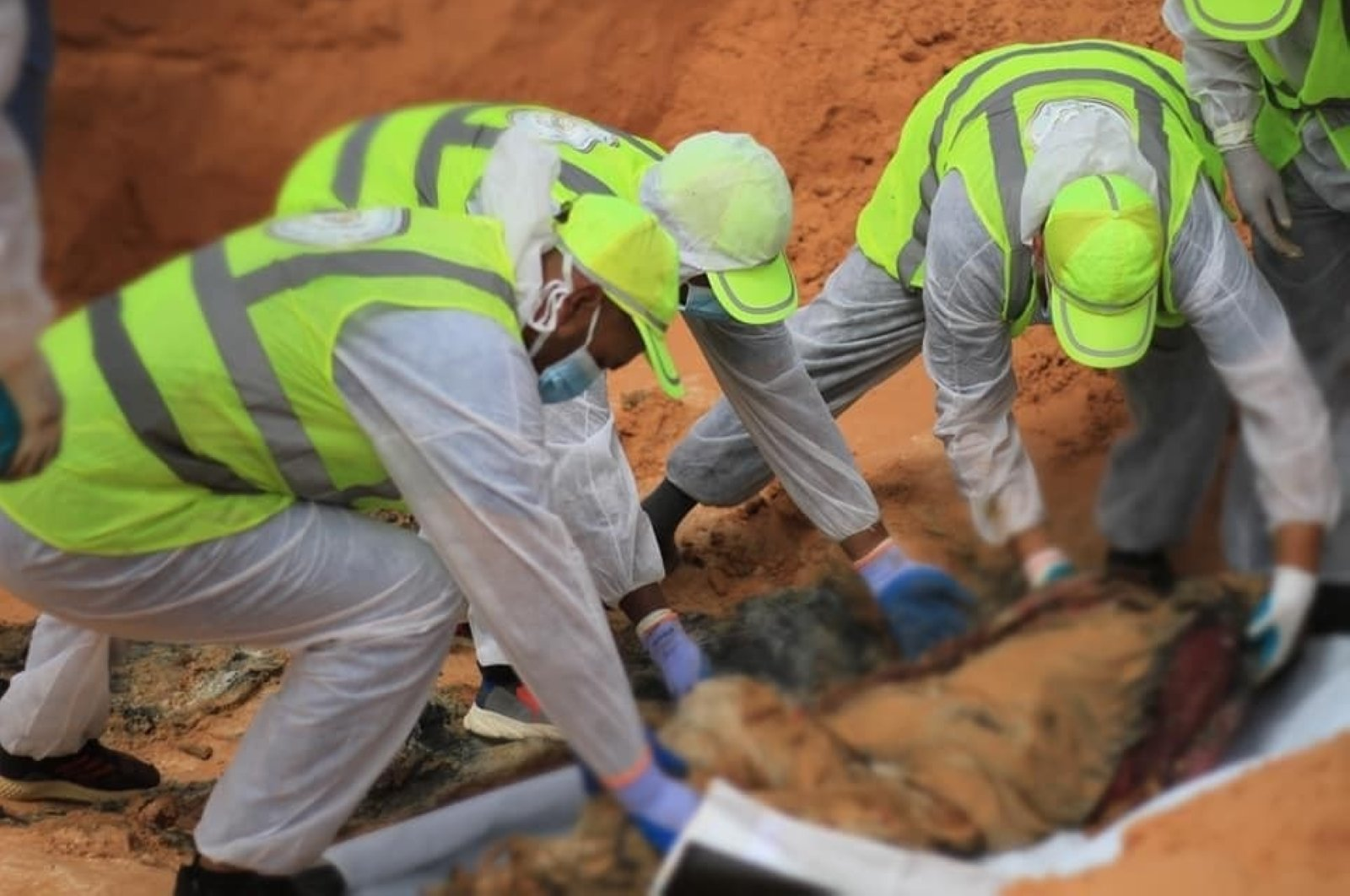 Libyan government workers uncover corpses found in a mass grave in Tarhuna, formerly occupied by the Haftar militias, Sept. 6, 2020. (IHA Photo)