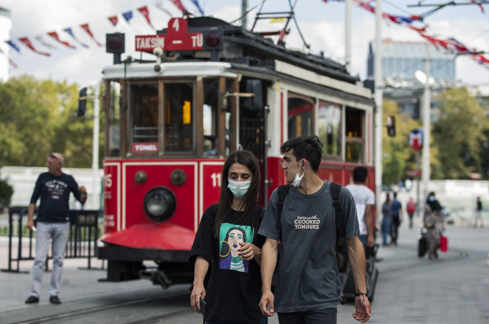 A woman wearing a protective mask and a man with a mask below his chin walk on a street in Istanbul, Turkey, Sept. 5, 2020. (DHA Photo)