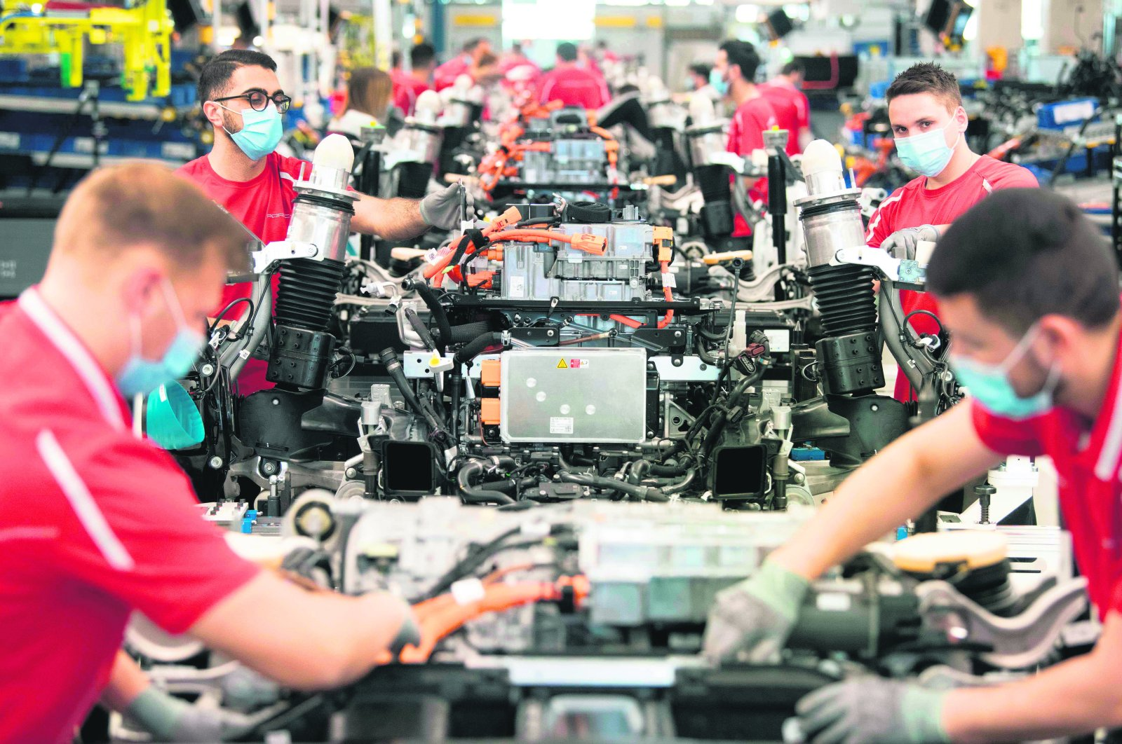 Employees of German car manufacturer Porsche wear face masks as they work on power trains for the Taycan full-electric sportscar at the production site in Stuttgart, southern Germany, on May 12, 2020. (AFP Photo)
