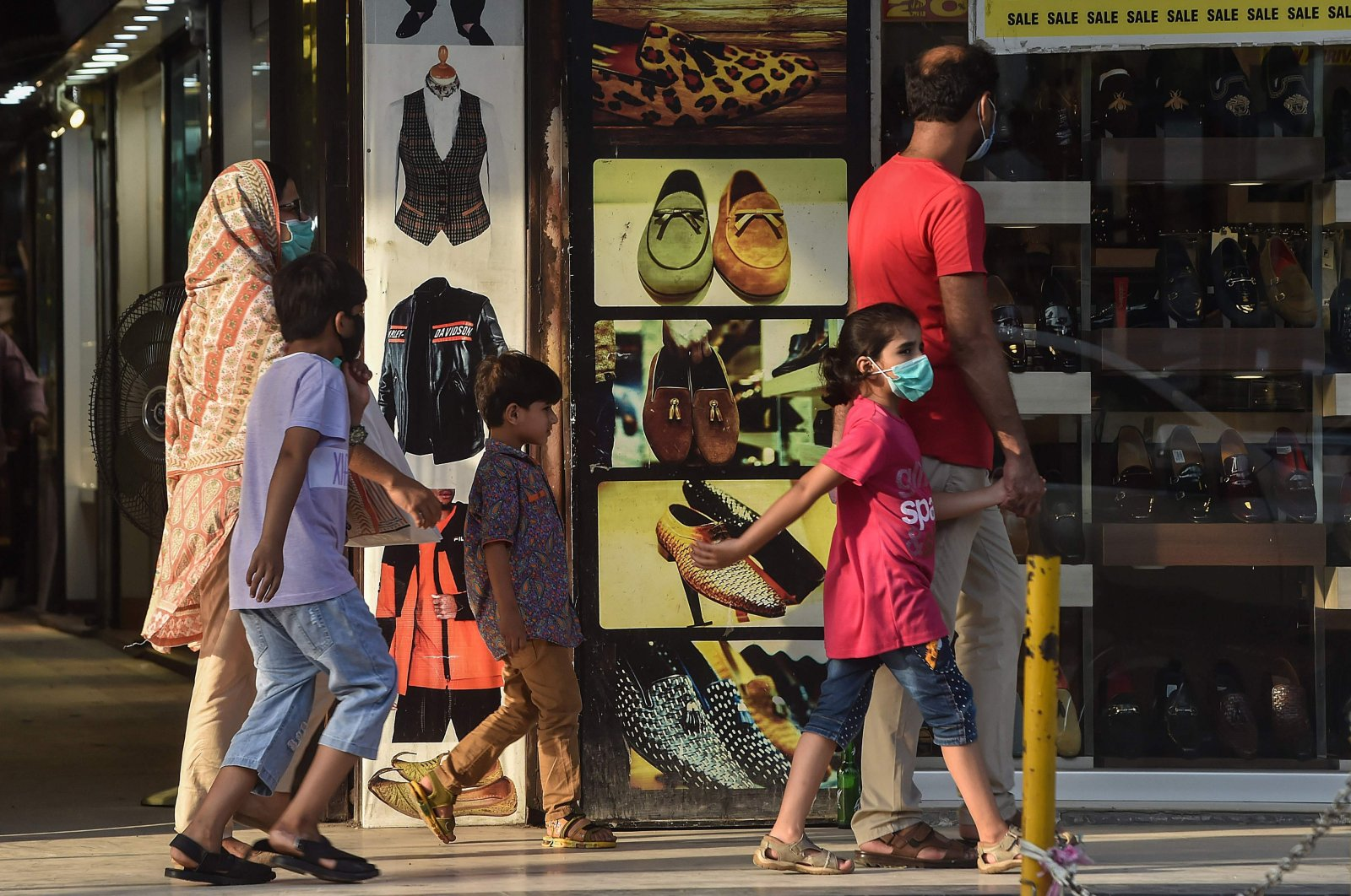 A family wearing facemasks as a preventive measure against the coronavirus shop at a market in Lahore, Aug. 31, 2020. (AFP Photo)