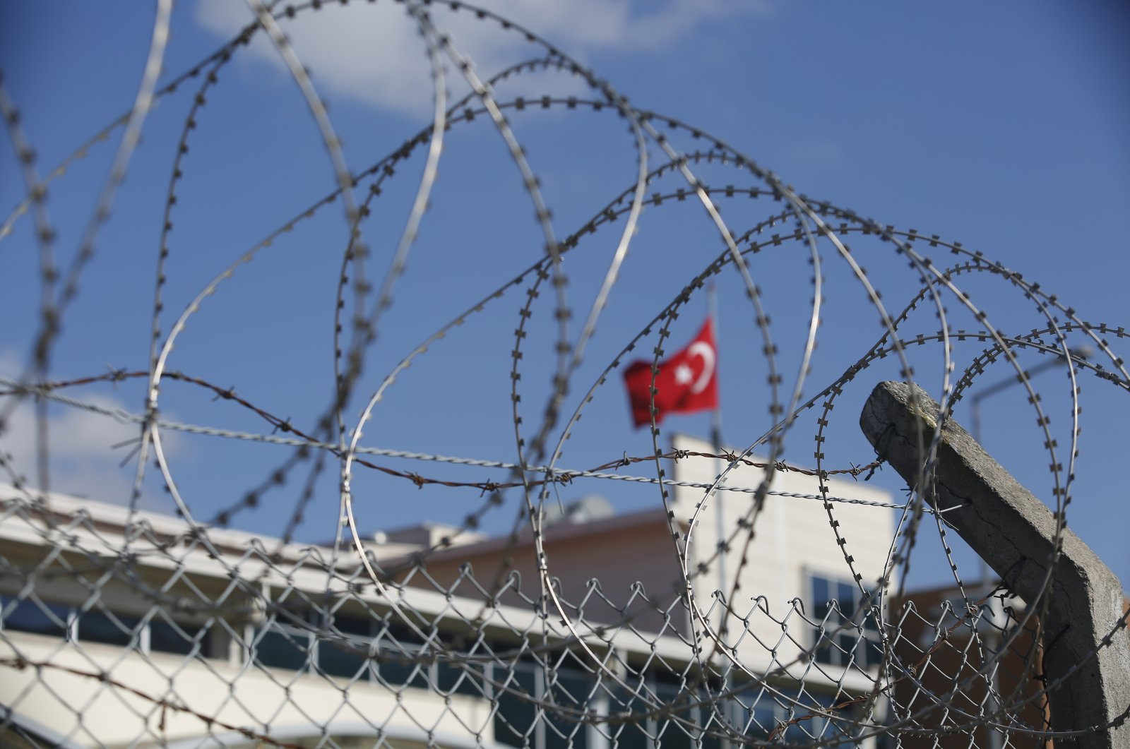 A Turkish flag behind the barbed-wire fence of the Silivri courthouse, in Silivri, outside Istanbul, Turkey, before the trial of Abdulkadir Masharipov,the main suspect in an attack that left 39 people dead at an Istanbul nightclub in 2017, Sept. 7, 2020. (AP Photo)