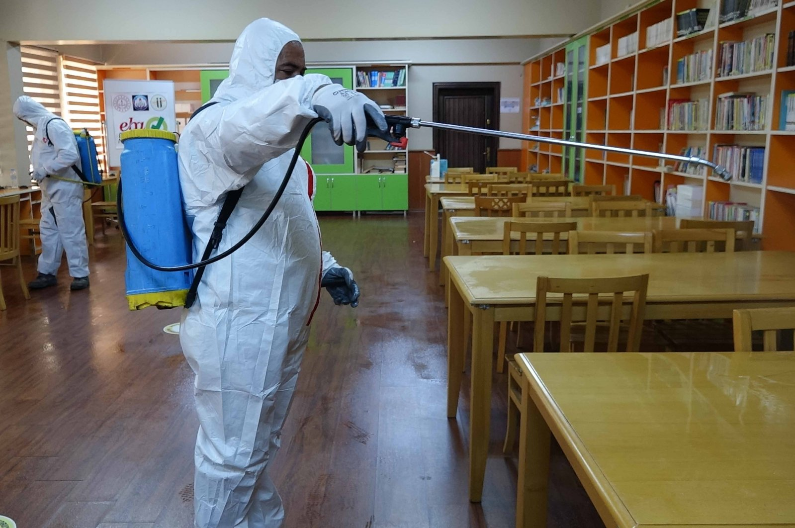 A man dressed in personal protective equiment (PPE) disinfects tables and bookshelves at a school in Adana province, southern Turkey, Sept. 3, 2020. (IHA Photo)