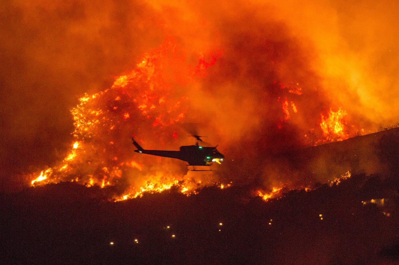 A helicopter prepares to drop water on a wildfire in Yucaipa, California, U.S., Sept. 5, 2020. (AP Photo)
