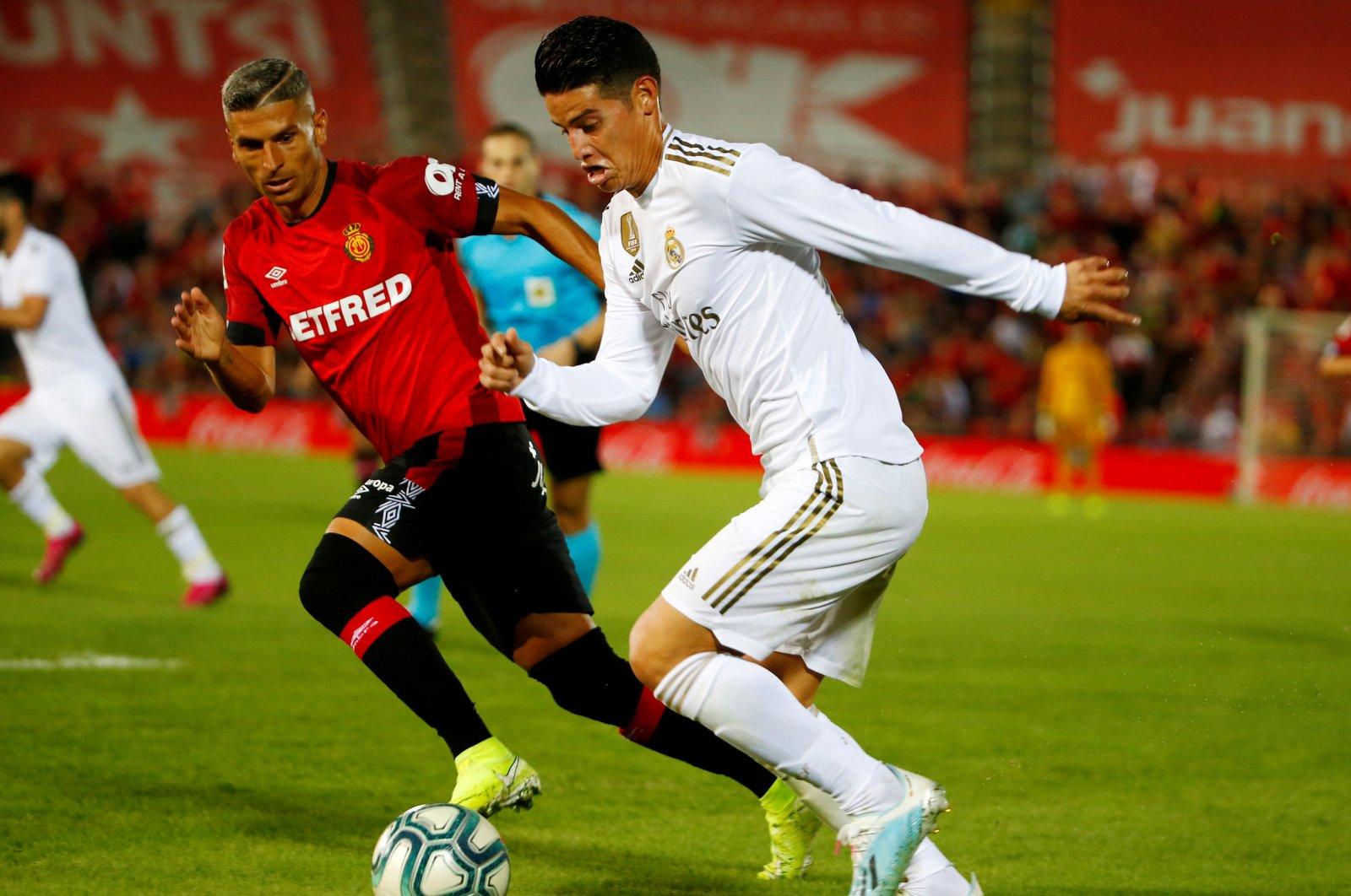 Real Madrid's James Rodriguez (R) dribbles the ball past Mallorca's Salva Sevilla at Iberostar Stadium, Palma, Spain, Oct. 19, 2019. (Reuters Photo)