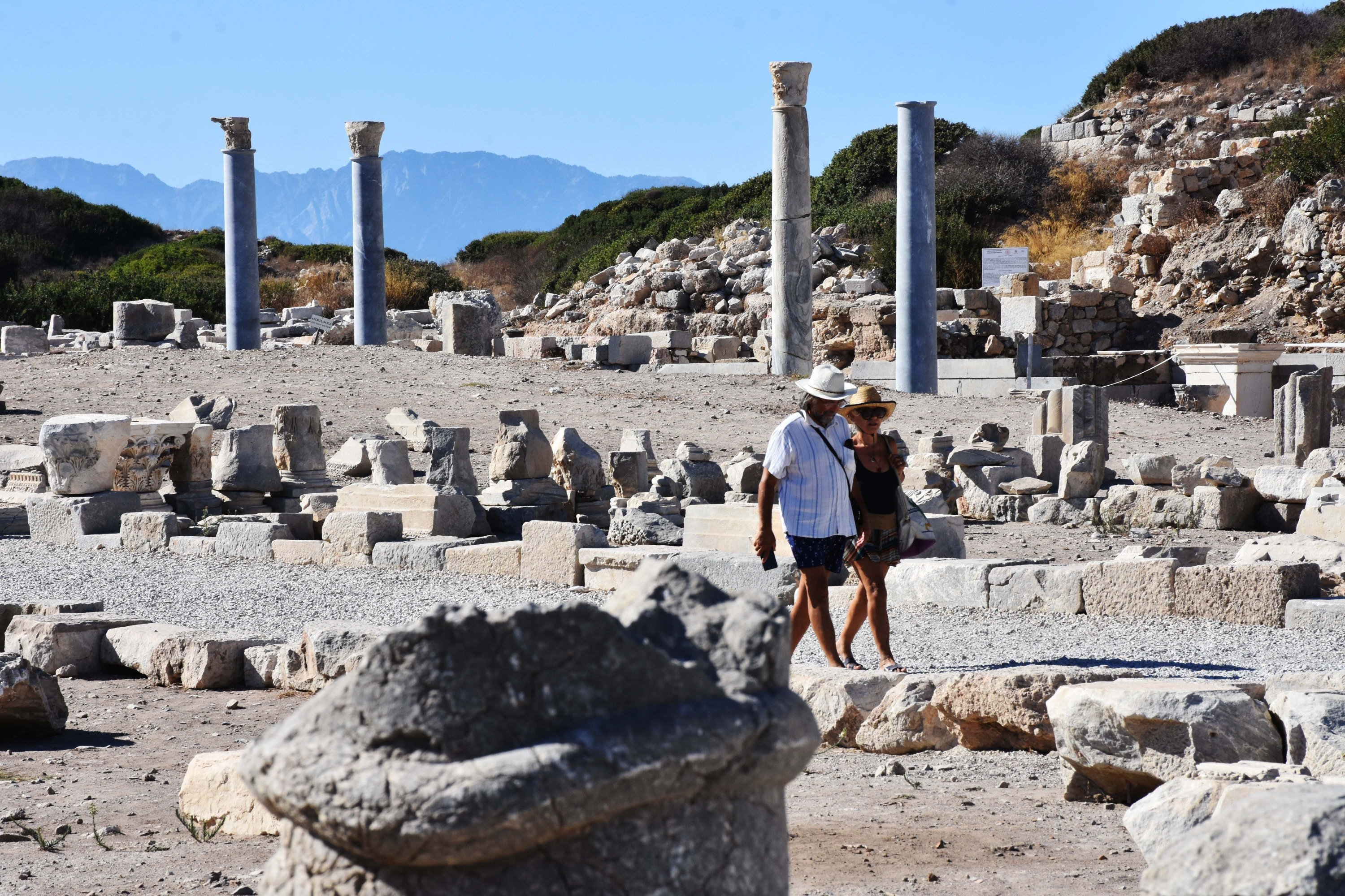 Two visitors walk among the historical ruins of the port street in the ancient city of Knidos, Muğla province, southwestern Turkey, Sept. 6, 2020. (AA Photo)