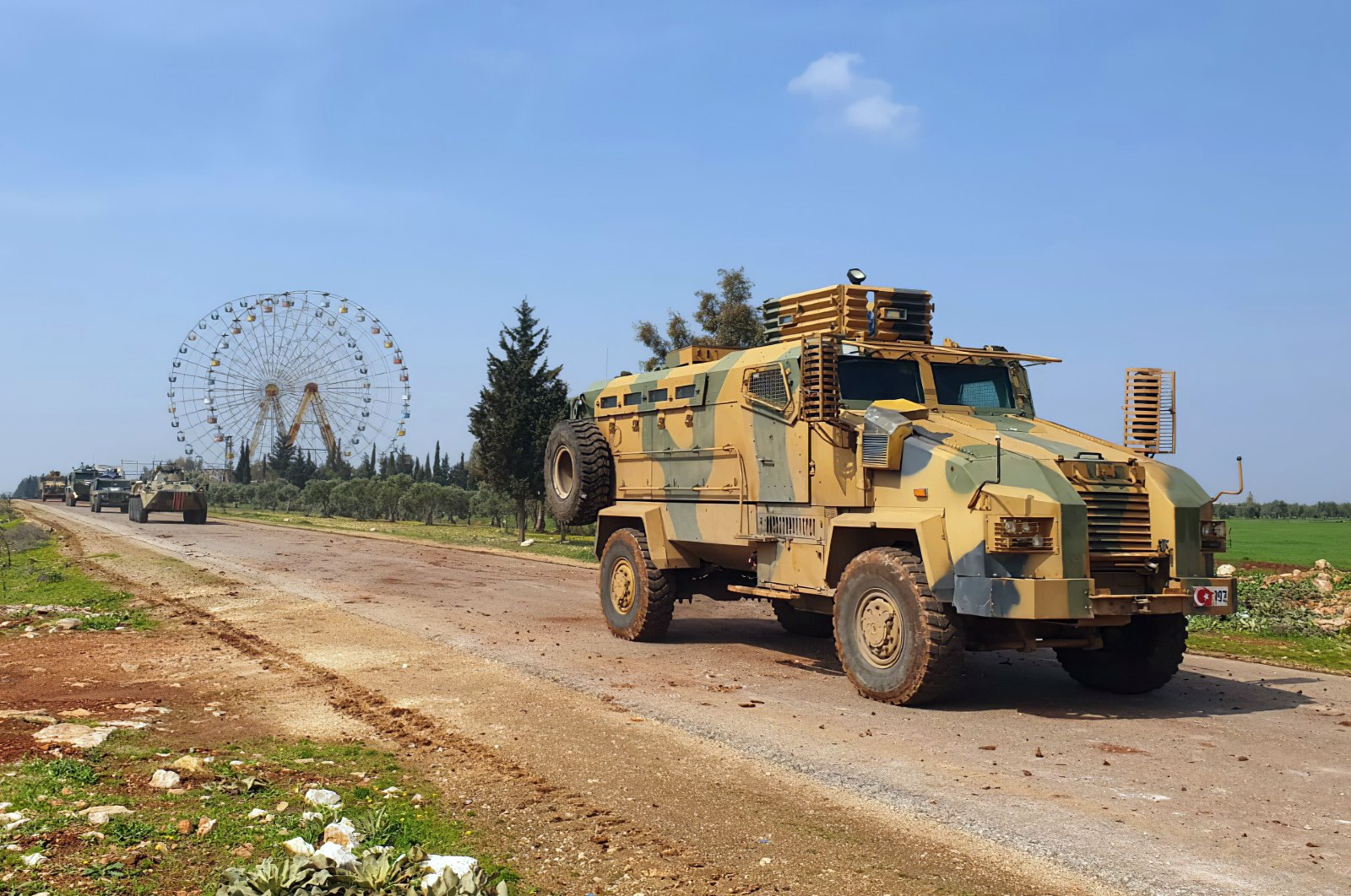 Turkish and Russian troops patrol on the M4 highway, which runs east-west through Idlib province, Syria, March 15, 2020. (Turkish Defense Ministry via AP)