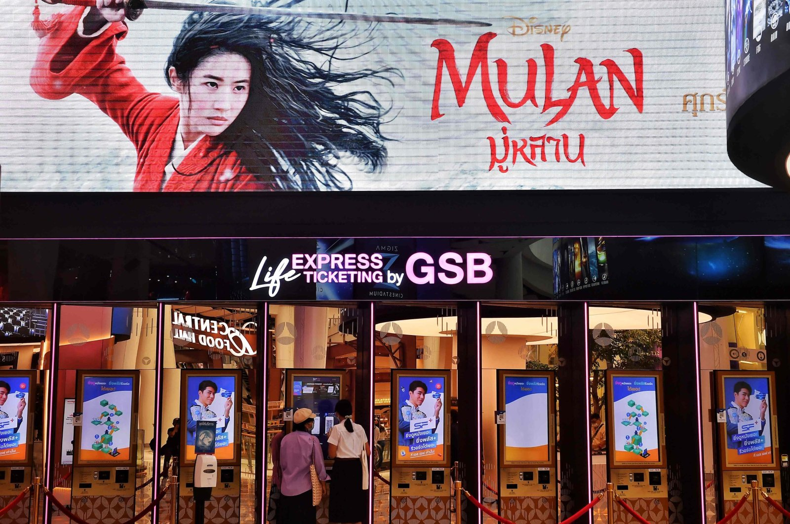 """People buy tickets for Disney's """"Mulan"""" film at a cinema inside a shopping mall in Bangkok, Thailand, Sept. 8, 2020. (AFP Photo)"""