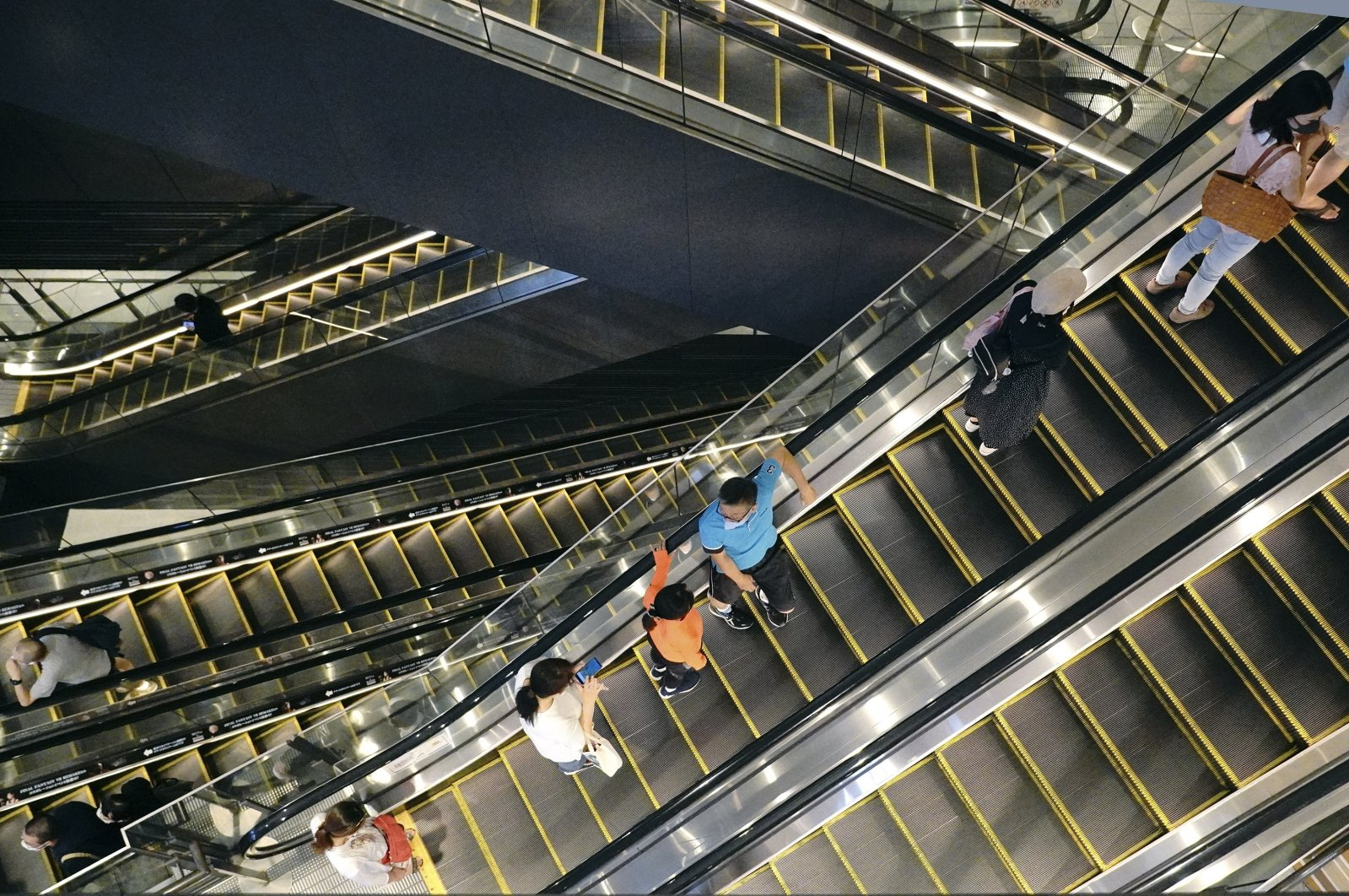 People take elevators at a shopping building in Tokyo on Aug. 24, 2020. (AP Photo)