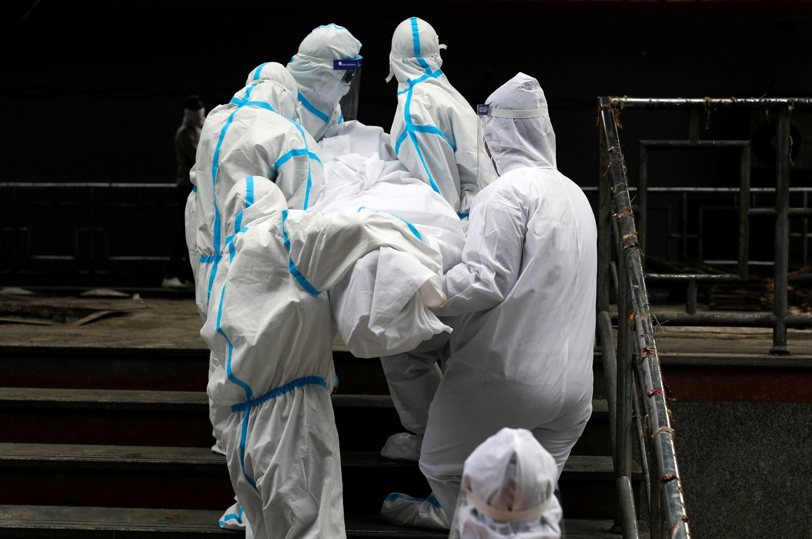 Health workers wearing personal protective equipment (PPE) carry the body of a man who died due to COVID-19, at a crematorium in New Delhi, India, Sept. 7, 2020. (Reuters Photo)