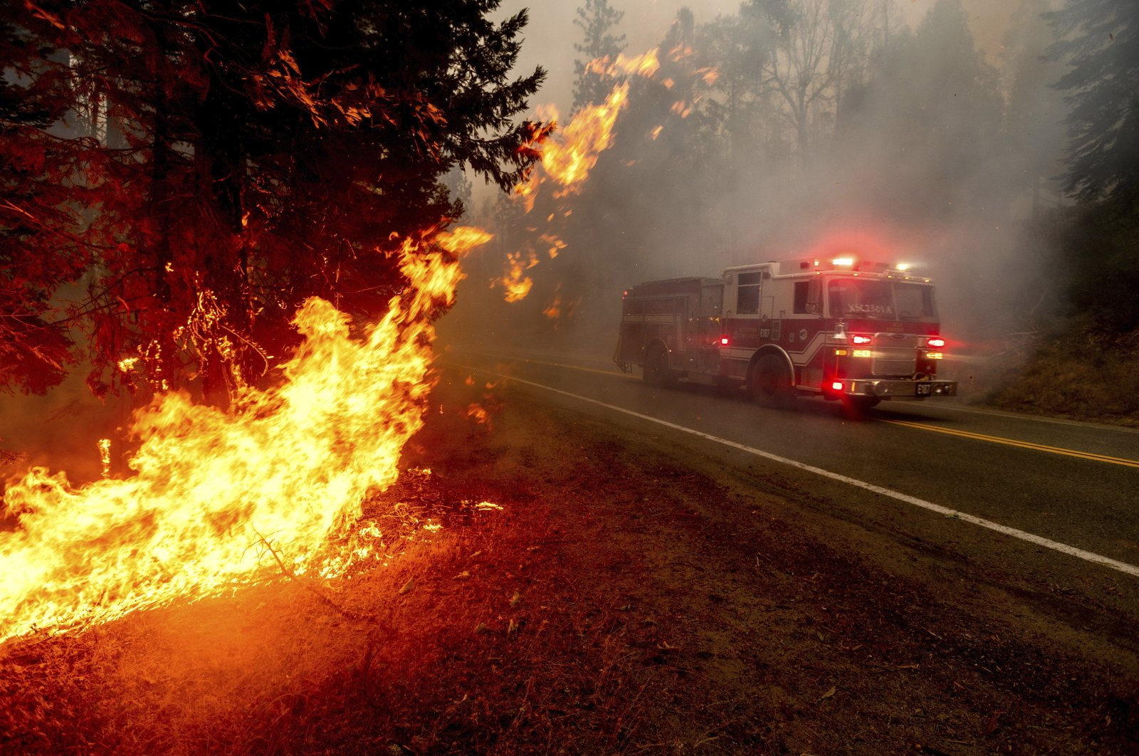 A firetruck drives along state Highway 168 while battling the Creek Fire in the Shaver Lake community of Fresno County, California, Sept. 7, 2020. (AP Photo)