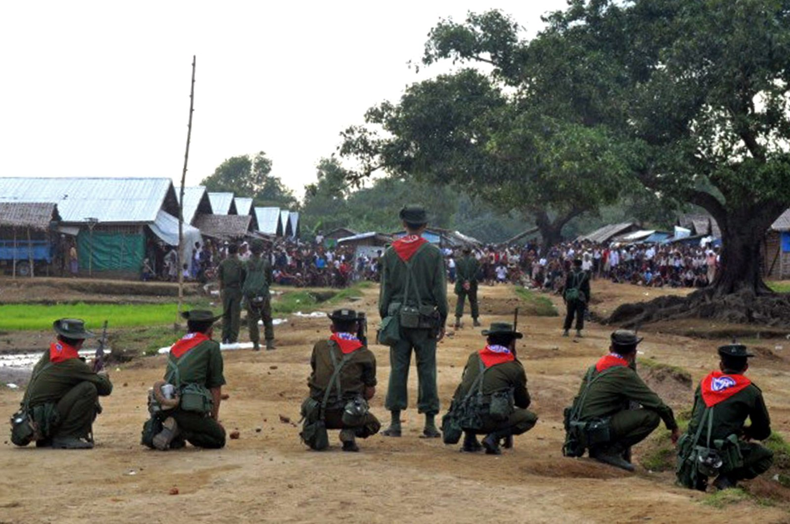Myanmar security force personnel stand guard while a mob (background) look on following unrest at an Internally Displaced People (IDP) camp for Muslim Rohingyas on the outskirts of Sittwe town in Rakhine State on Aug. 9, 2013. (AFP Photo)