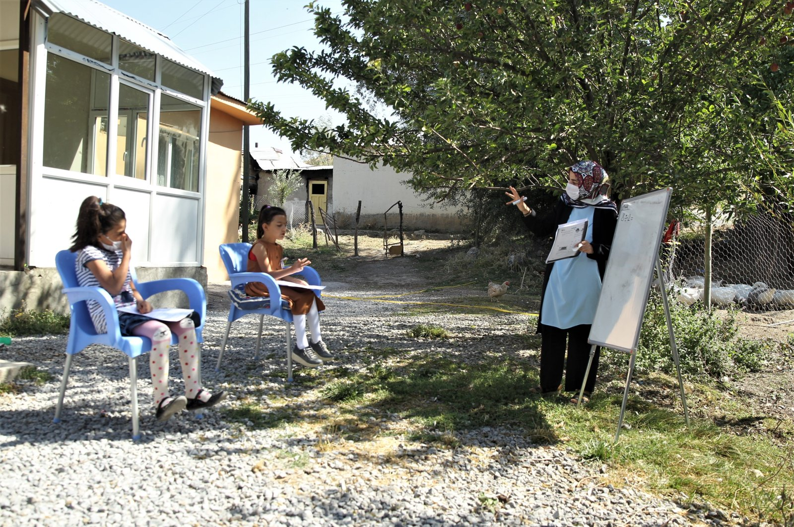 Gamze Arslan teaches a class of two students in their home's courtyard, in Van, eastern Turkey, Sept. 7, 2020. (AA Photo)