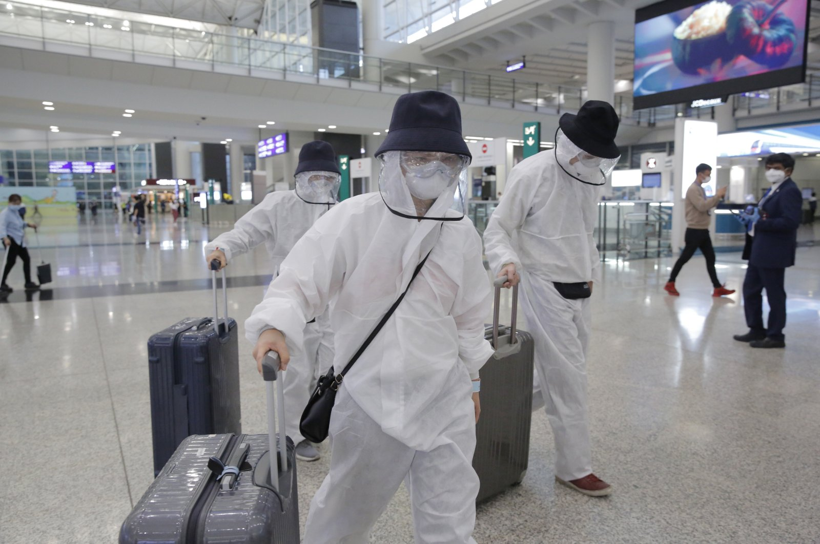 Passengers wear suits and face masks to protect against the coronavirus as they arrive at the Hong Kong airport, March 23, 2020. (AP Photo)
