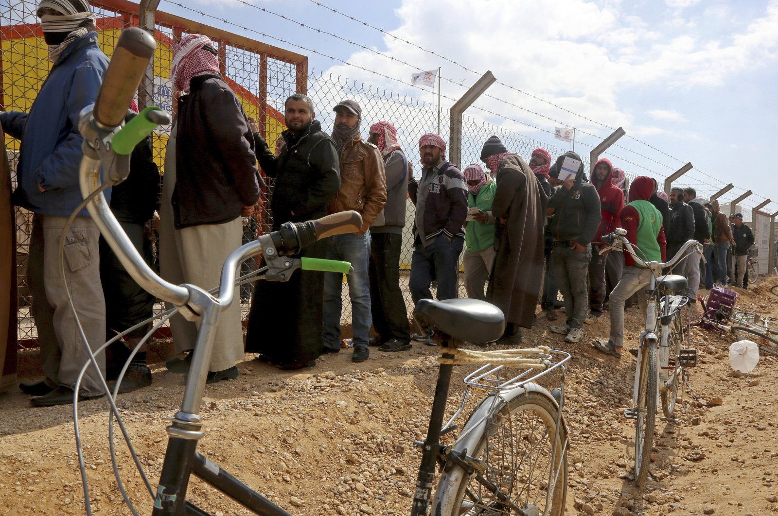 Syrian refugees line up to register their names at an employment office, at the Azraq Refugee Camp, 100 kilometers (62 miles) east of Amman, Jordan, Feb. 18, 2018. (AP Photo)
