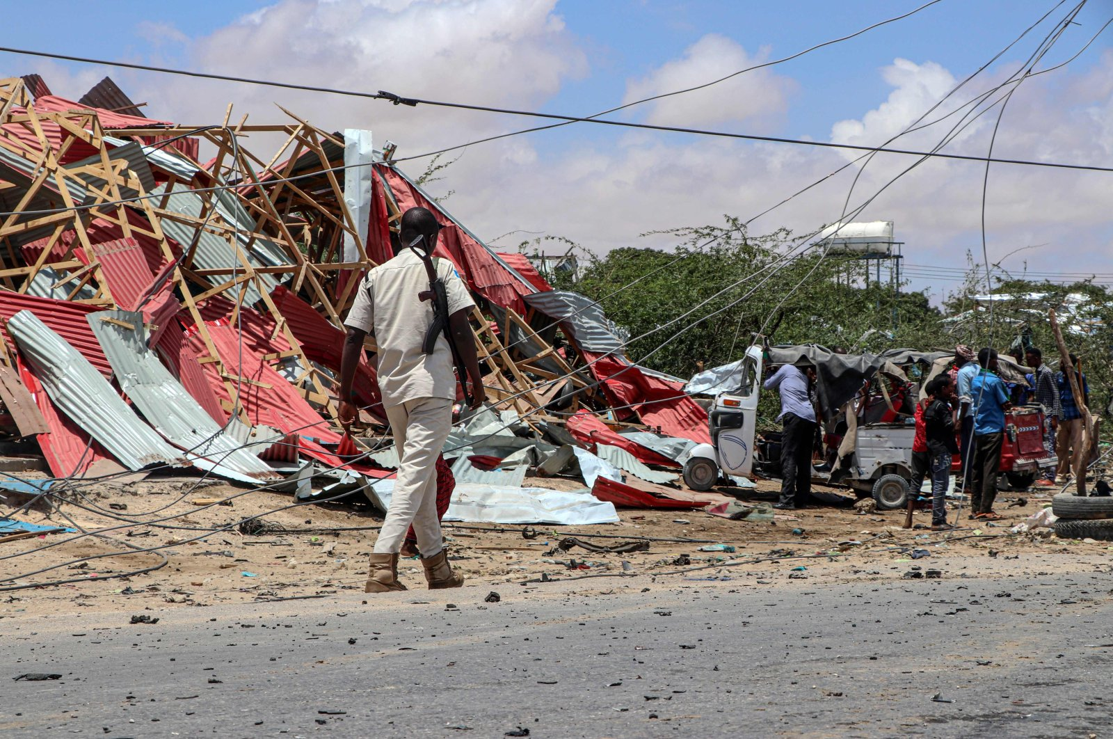 A Somali police officer patrols (L) as bystanders gather at the site of a suicide car bombing that targeted a European Union vehicle convoy in Mogadishu, Somalia, Sept. 30, 2019. (AFP Photo)