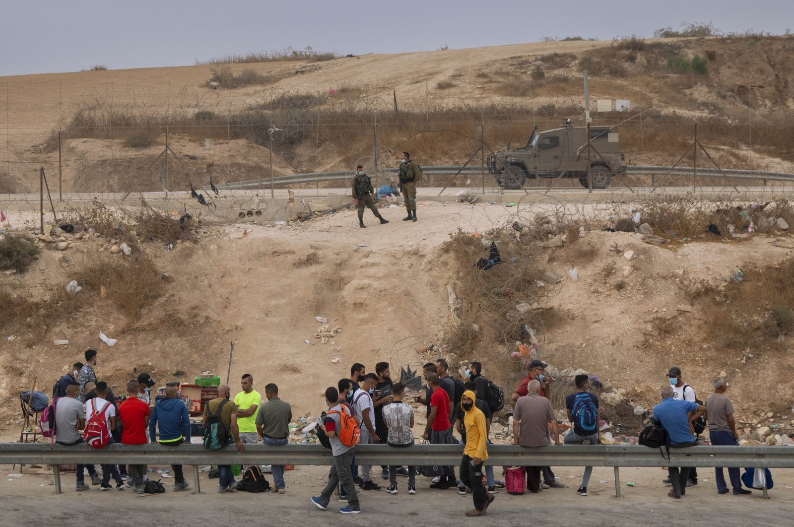 Israeli soldiers prevent Palestinian laborers from crossing illegally into Israel from the West Bank through an opening in a fence, south of the West Bank town of Hebron, Sept. 6, 2020. (AP Photo)