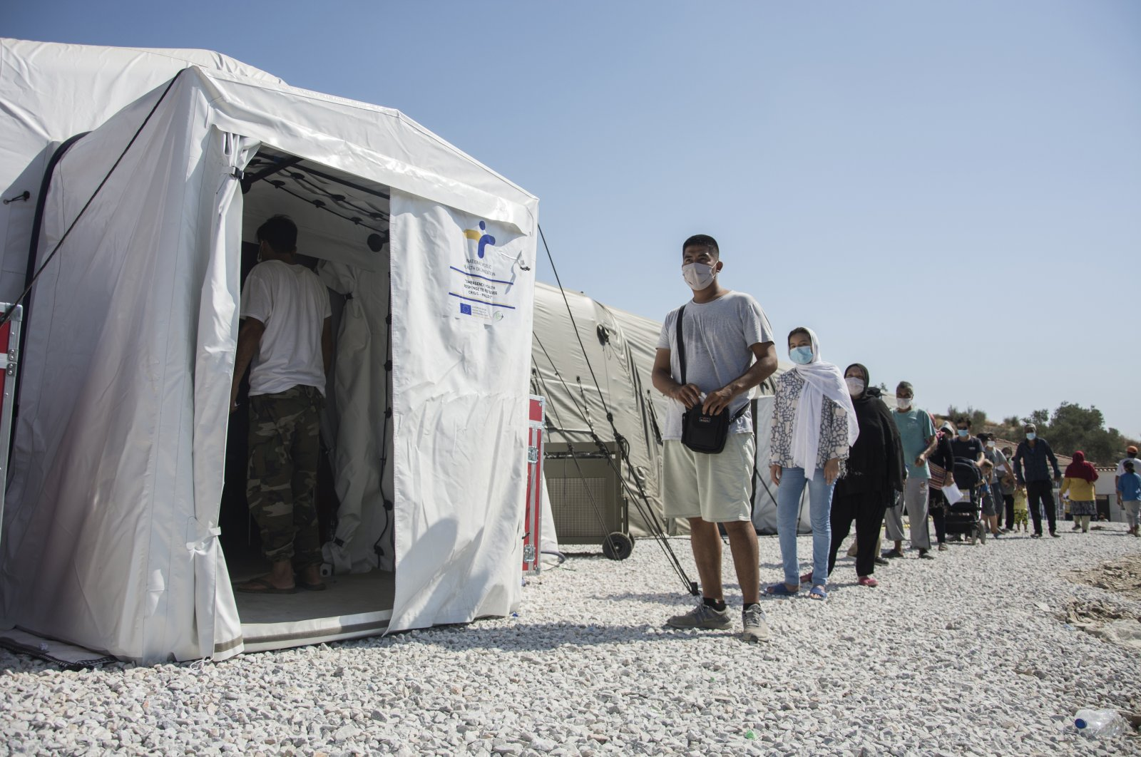 Migrants wait in a queue to do tests for the new coronavirus in Moria refugee camp on the northeastern Aegean island of Lesbos, Greece, Sept. 4, 2020. (AP Photo)