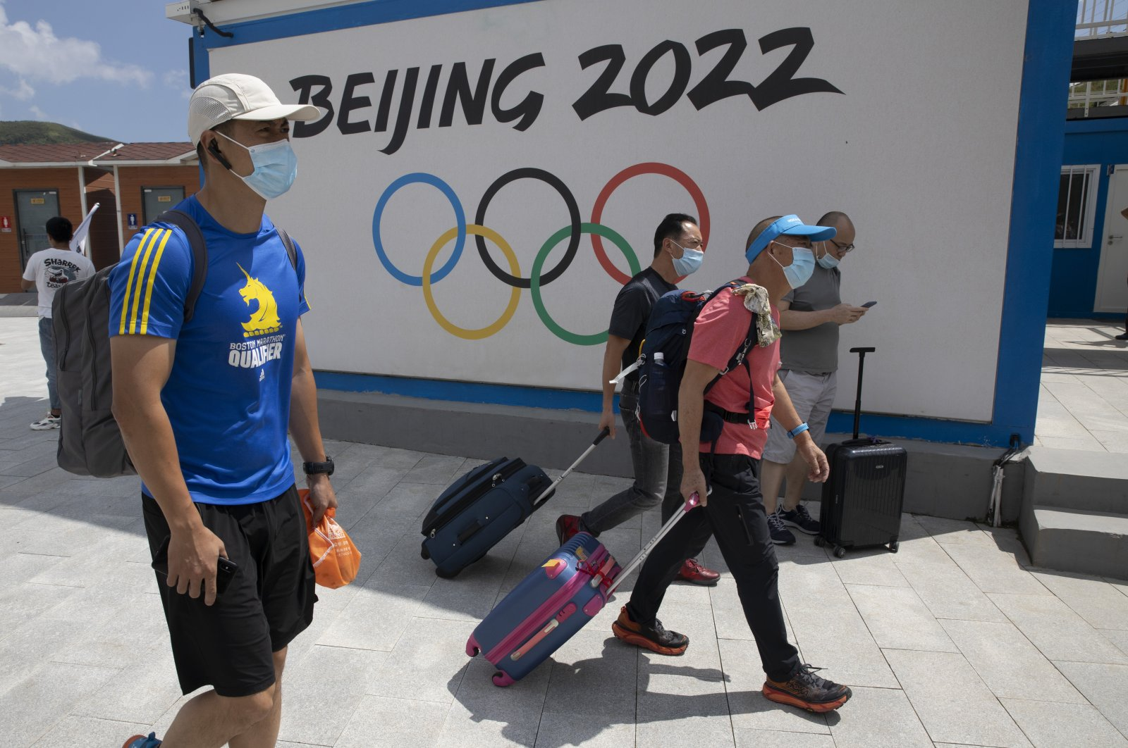 Visitors to Chongli, one of the venues for the Beijing 2022 Winter Olympics, past by the Olympics logo in Chongli in northern China's Hebei Province on Thursday, Aug. 13, 2020. (AP Photo)