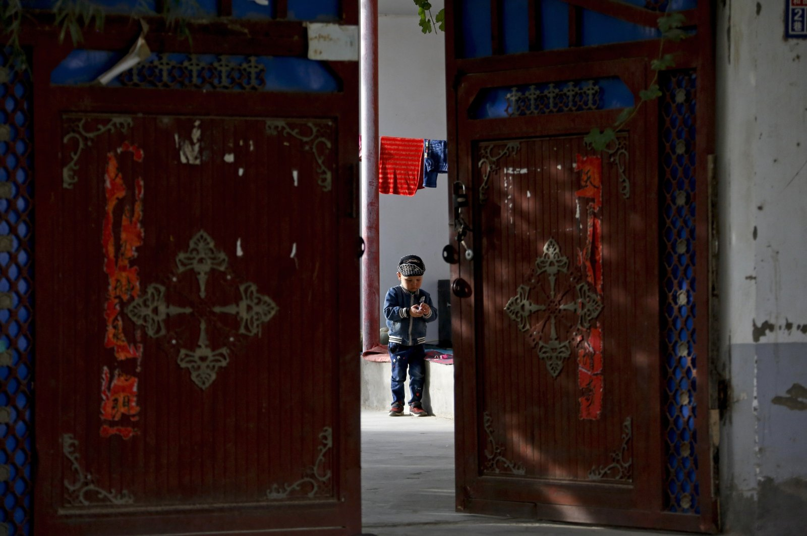 A Uighur child plays alone in the courtyard of a home at the Unity New Village in Hotan, in western China's Xinjiang region, Sept. 20, 2018. (AP Photo)