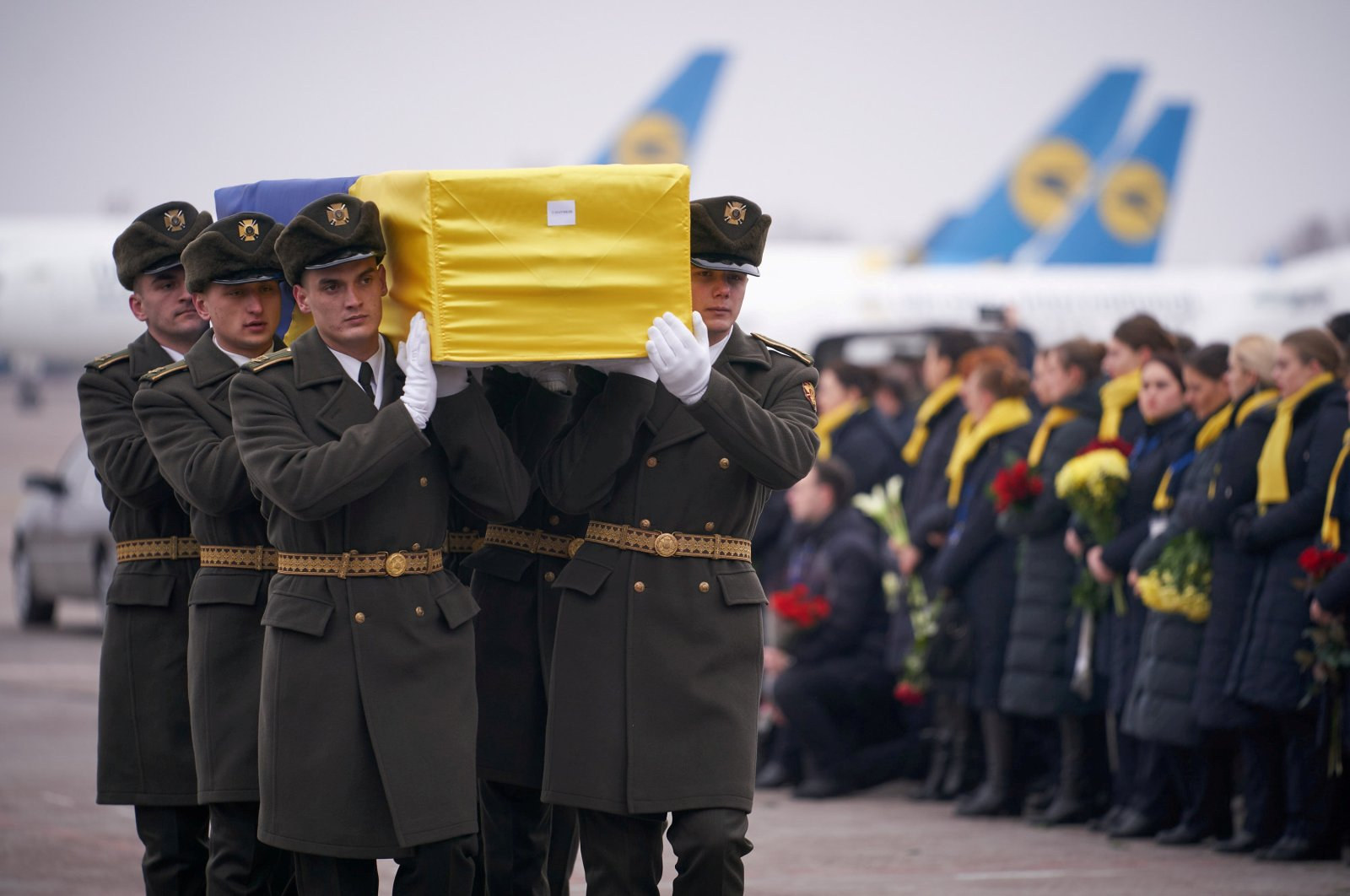 Soldiers carry a coffin containing the remains of one of the 11 Ukrainian victims of the Ukraine International Airlines flight 752 plane disaster during a memorial ceremony at the Boryspil International Airport, outside Kyiv, Ukraine, Jan. 19, 2020. (Ukrainian Presidential Press Service via Reuters)