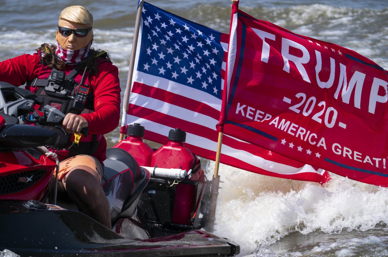 "A person dressed as President Donald Trump drives a jet ski during the ""Nation's Capital Trumptilla Boat Parade"" on the Potomac River in Washington, DC, Sept. 6, 2020. (AFP Photo)"
