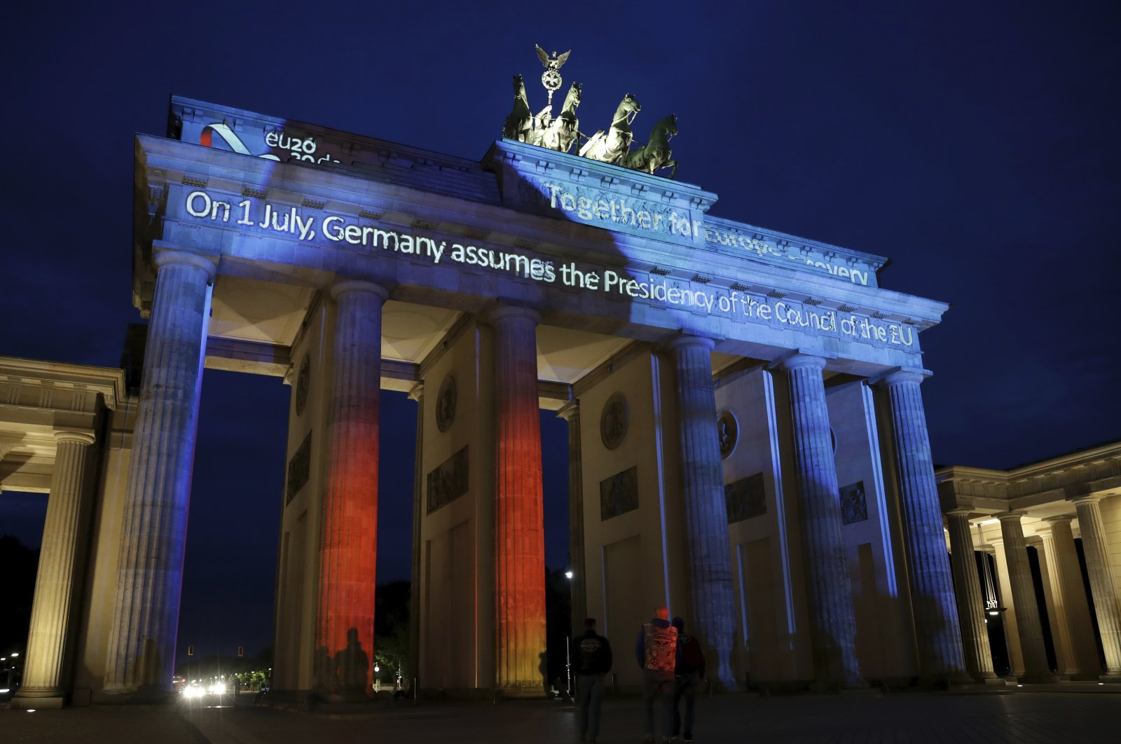 """The Brandenburg Gate is illuminated with the slogan """"On 1 July, Germany assumes the Presidency of the Council of the EU"""" on the eve of the official start of Germany's six-month EU presidency, in Berlin, Germany, June 30, 2020. (AP Photo)"""