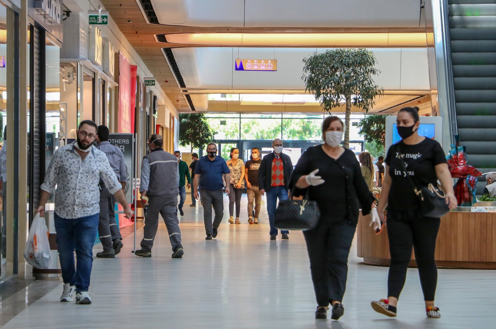 People wearing protective masks walk inside a shopping mall in Antalya, southern Turkey, May 13, 2020. (DHA Photo)