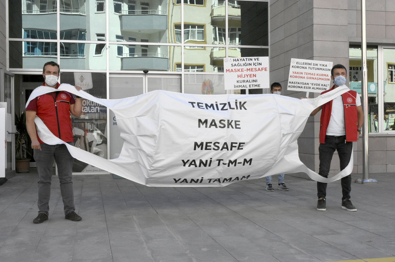 """Two young activists hold a banner in the shape of a mask with the message """"hygiene, mask, distance"""" for public awareness, in Gümüşhane, northern Turkey, Sept. 8, 2020. (AA Photo)"""
