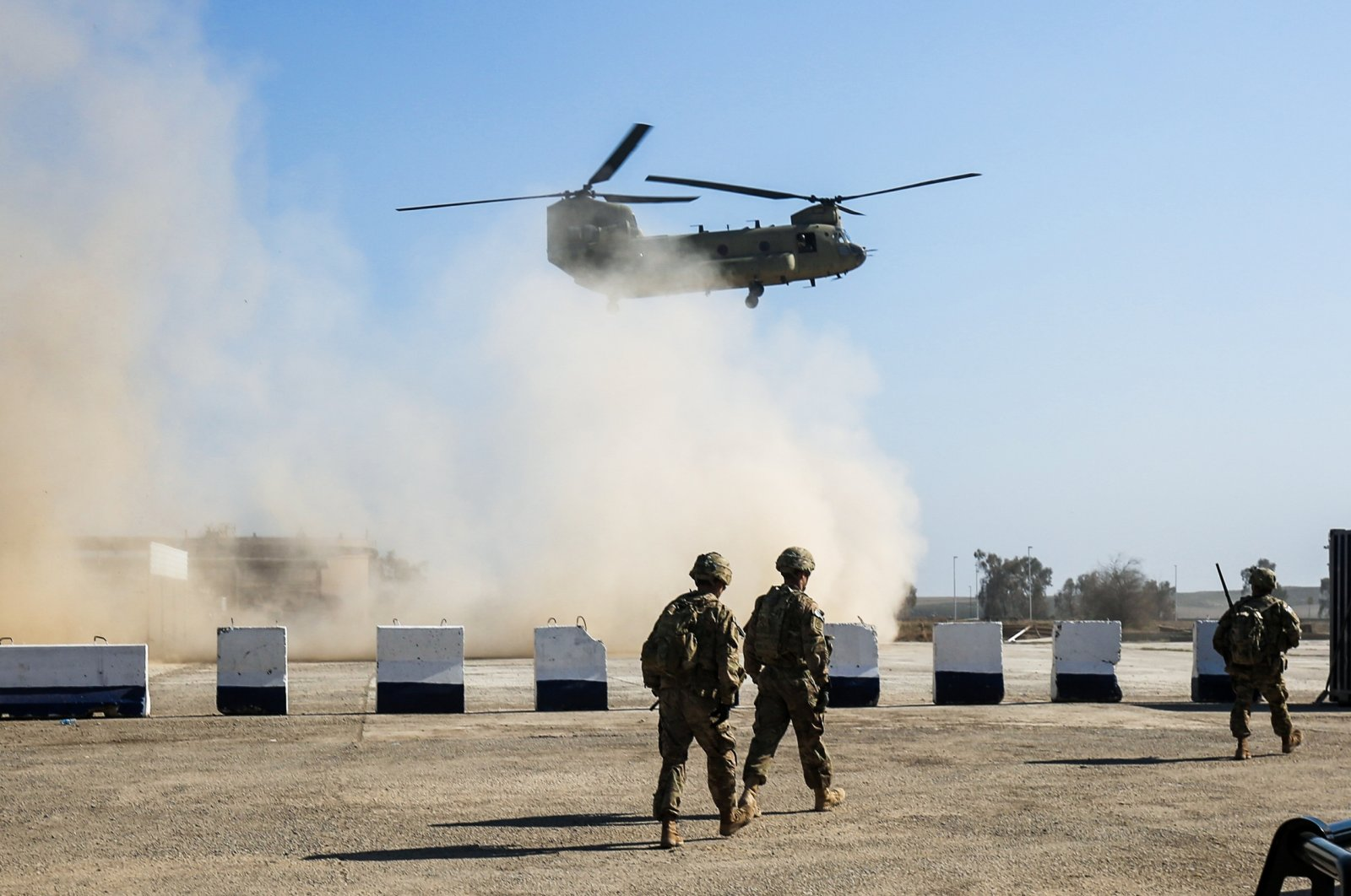 U.S. troops walk as a U.S. Army C-47 Chinook helicopter flies over the village of Oreij, south of Mosul, Feb. 22, 2017. (AFP Photo)