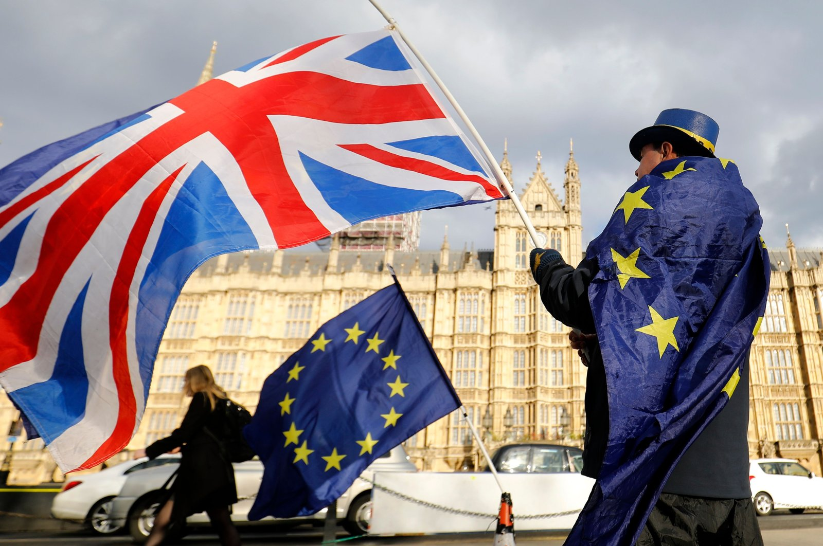 In this file photo, an anti-Brexit demonstrator waves a British flag alongside a European Union flag outside the Houses of Parliament in London, March 28, 2018. (AFP Photo)