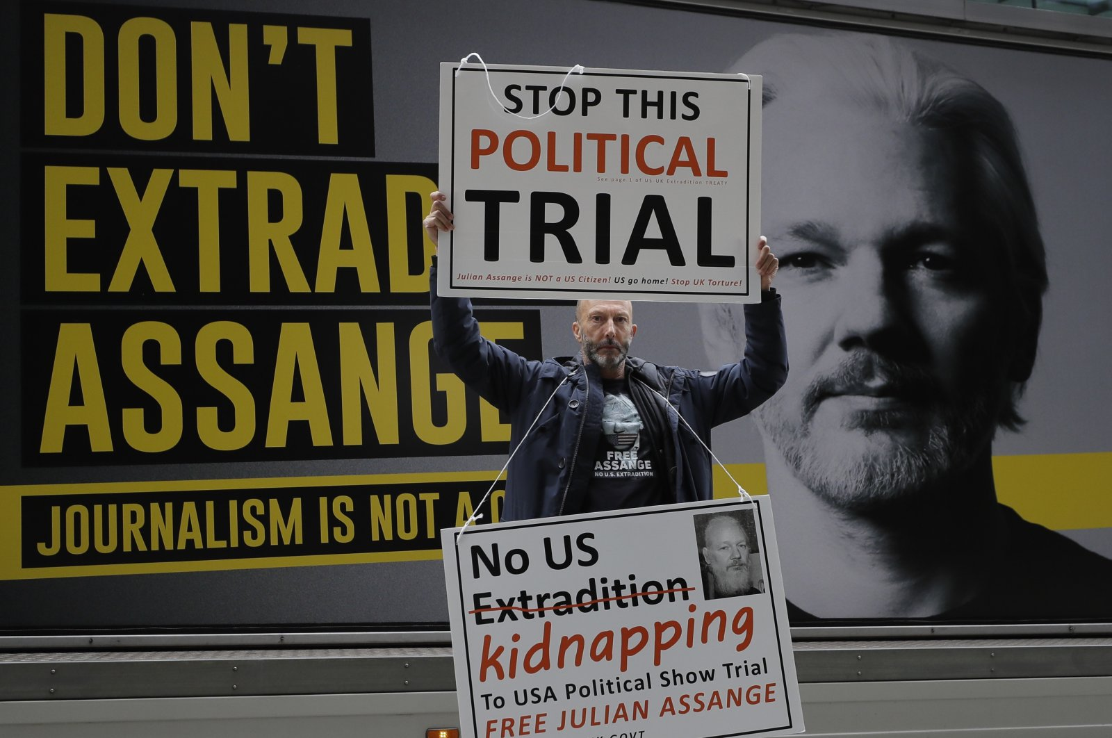 A demonstrator holds placards near the Central Criminal Court Old Bailey in London, Sept. 8, 2020. (AP Photo)