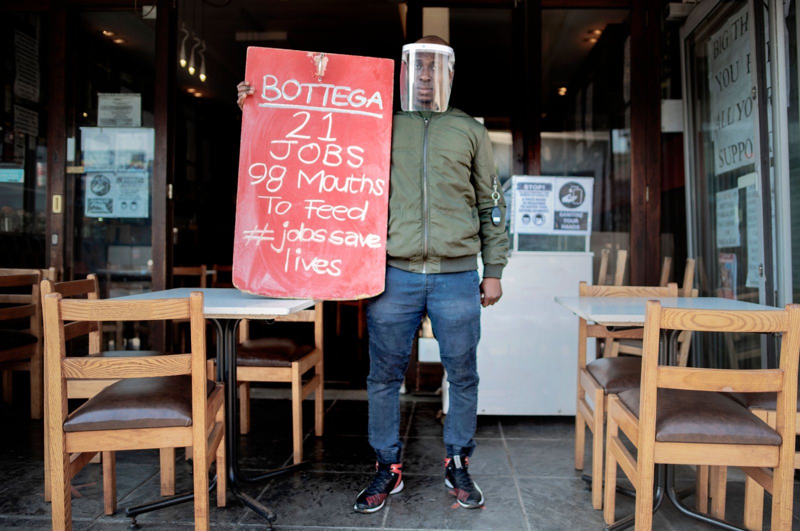 The manager of a restaurant holds a banner during a national protest against the national lockdown regulations the South African government has issued to fight the rise of coronavirus cases, Johannesburg, South Africa, July 22, 2020. (AFP Photo)