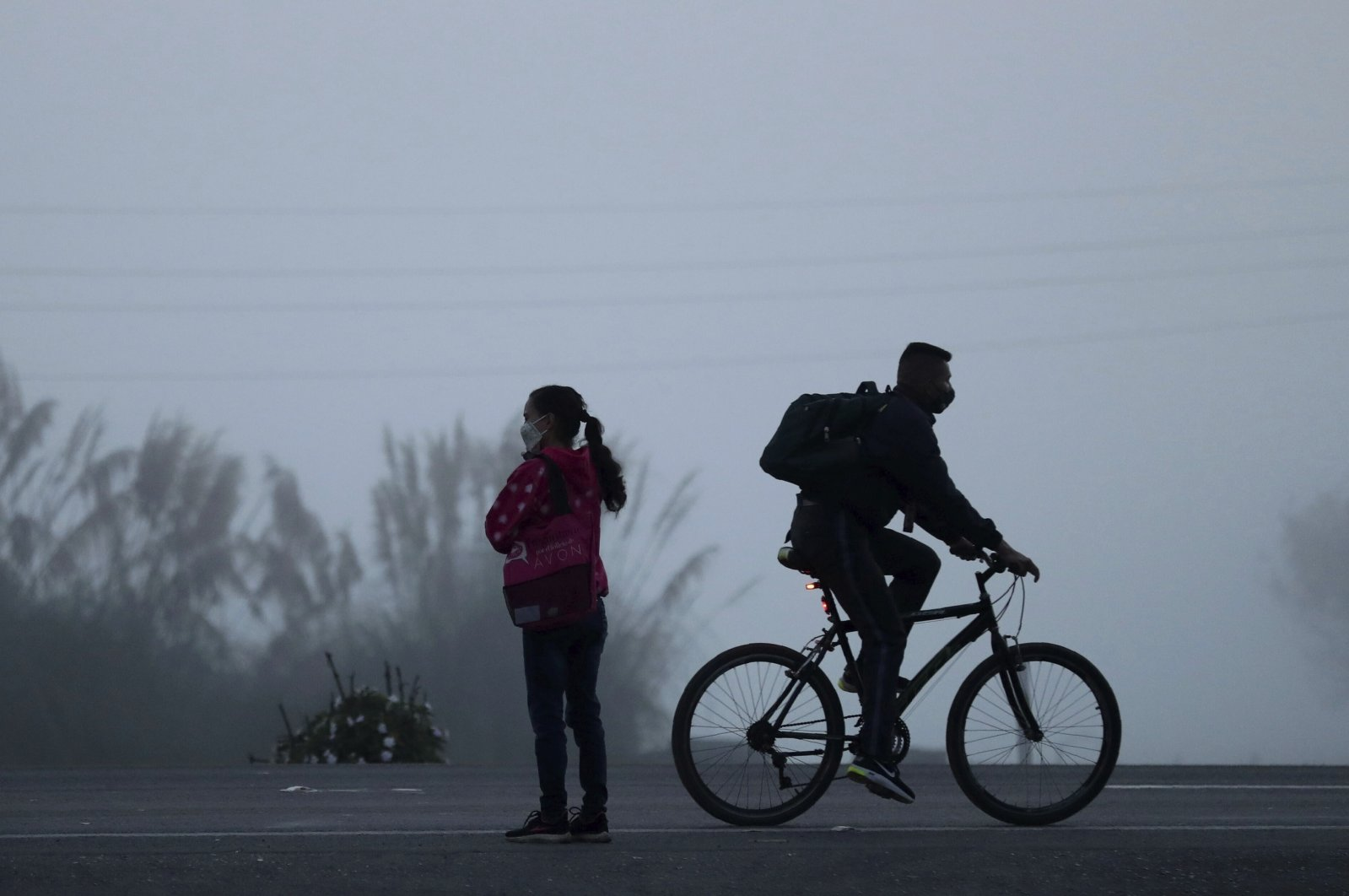 A man rides his bicycle to his workplace, in Madrid, Colombia, Aug. 25, 2020. (AP Photo)