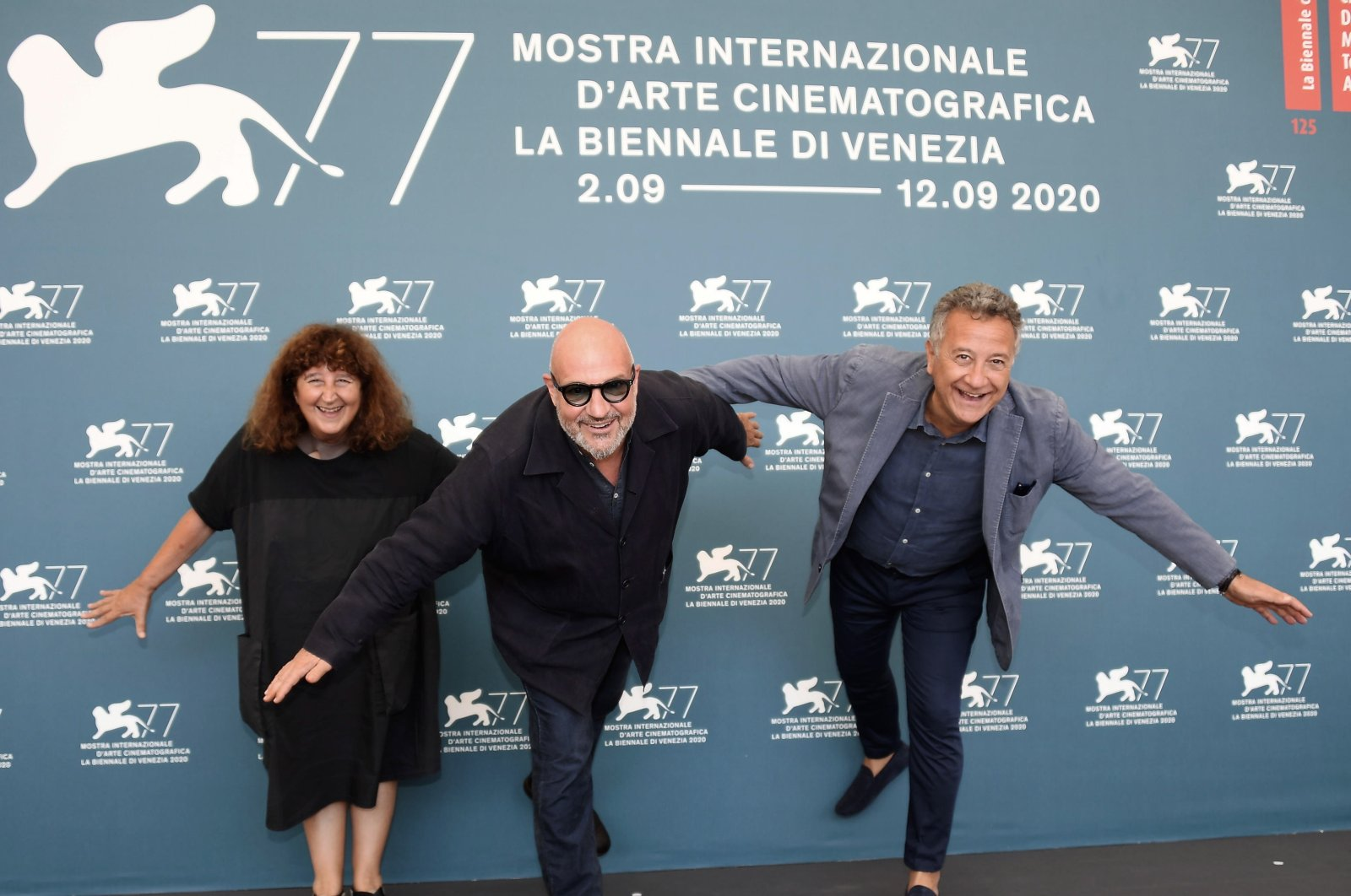 """Italian filmmaker Gianfranco Rosi (C), Italian producers Donatella Palermo (L) and Paolo Del Brocco (R), pose at a photocall for """"Notturno"""" during the 77th annual Venice International Film Festival, in Venice, Italy, Sept. 8, 2020. (EPA Photo)"""